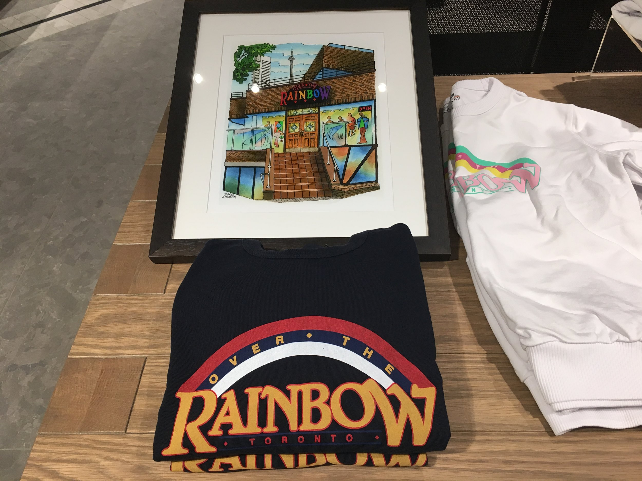 A framed photo of the former 101 Yorkville Avenue Over the Rainbow storefront, as well as sweatshirts with the former branding. Photo: Craig Patterson