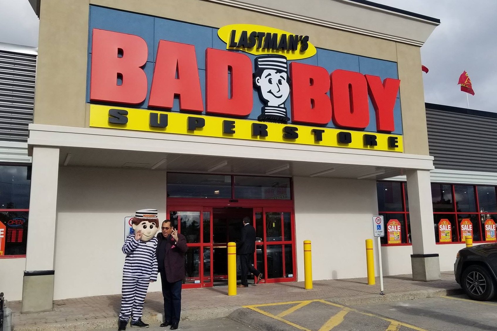 BLAYNE LASTMAN AND THE BAD BOY FURNITURE MASCOT OUTSIDE THEIR BURLINGTON, ON LOCATION PHOTO: LASTMAN'S BAD BOY VIA FACEBOOK