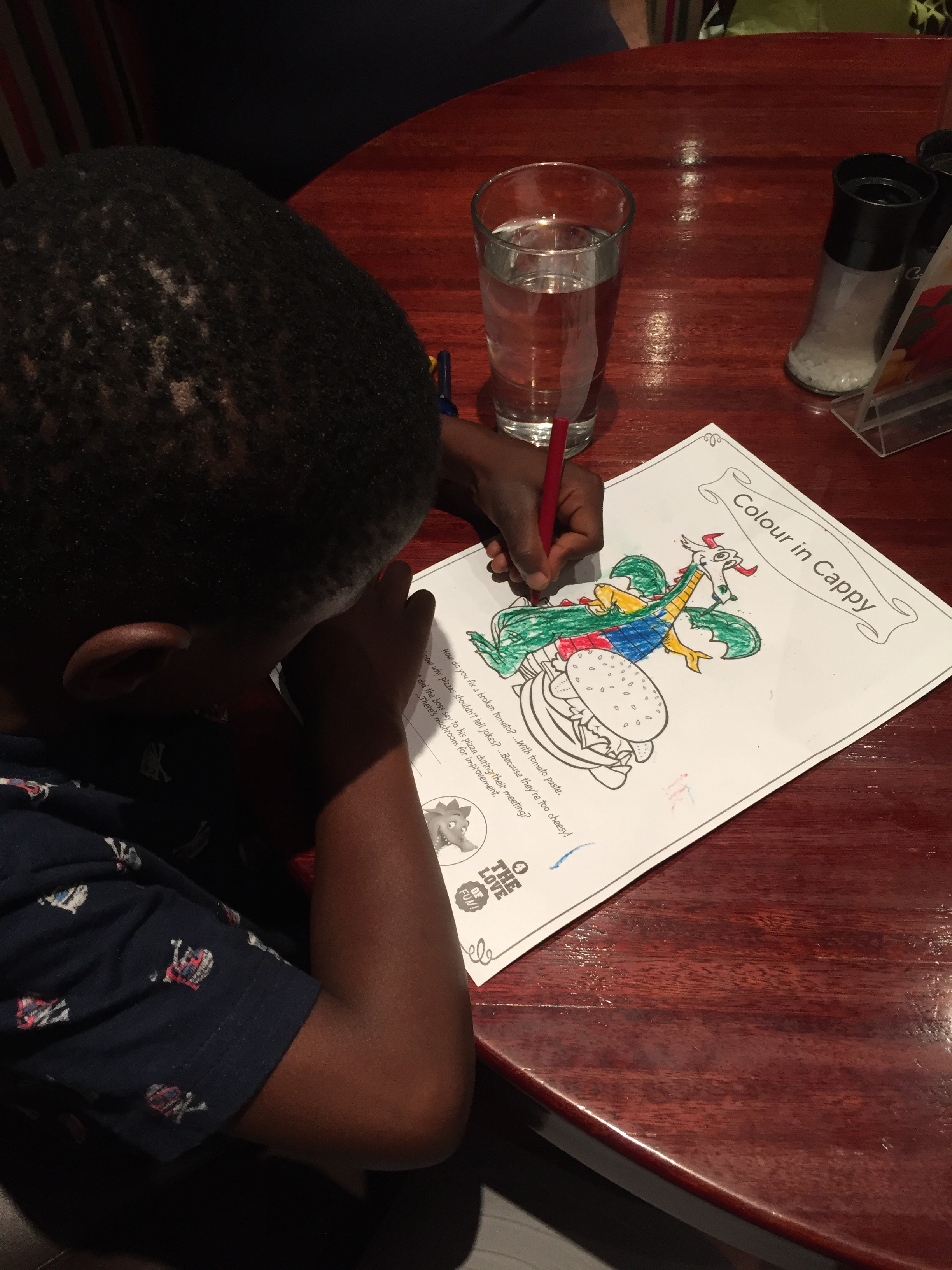Coloring at dinner. He's wearing a new t-shirt with scuba skull and crossbones.