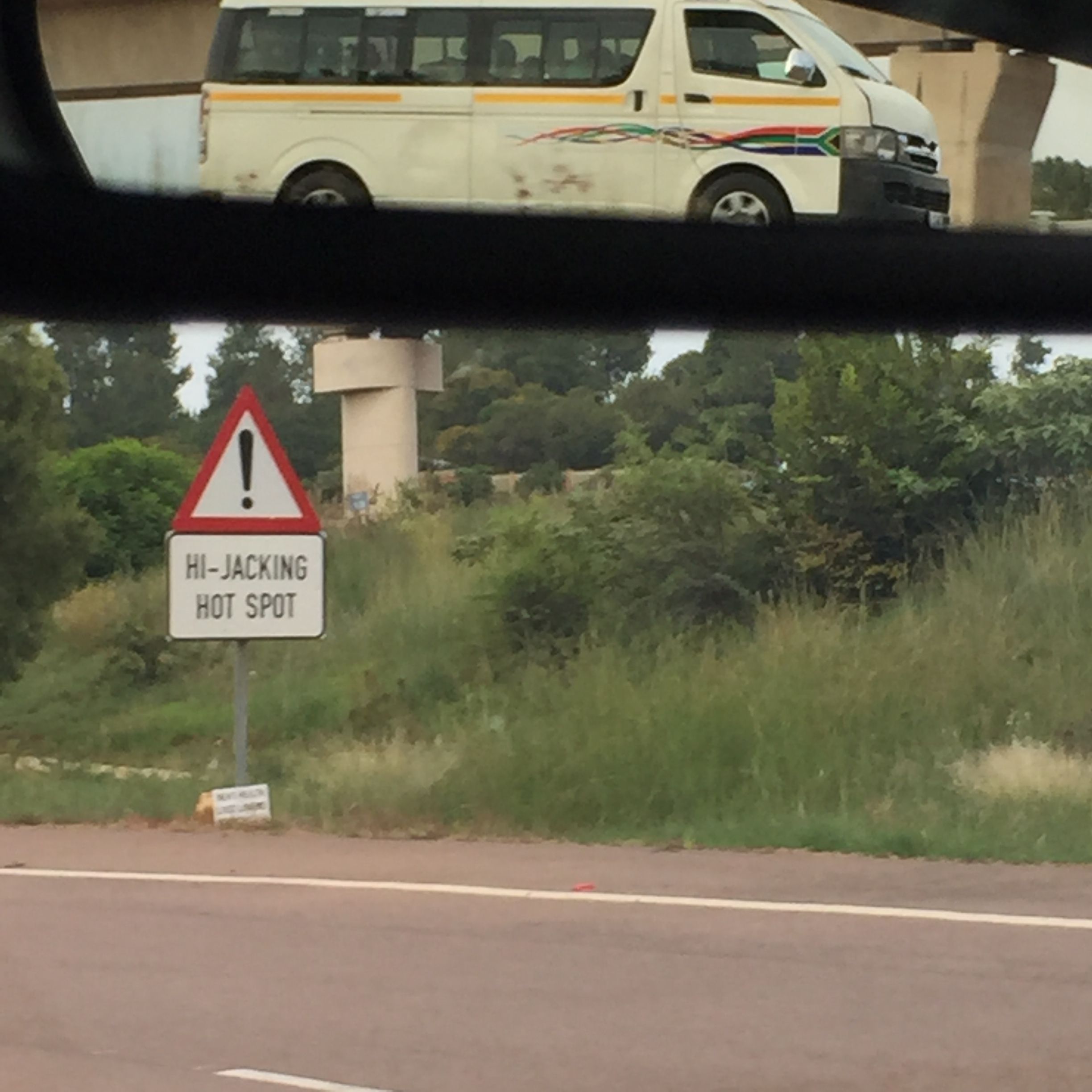 I was trying to take a photo of this terrifying road sign, but also managed to capture a speeding taxi in our rearview mirror.