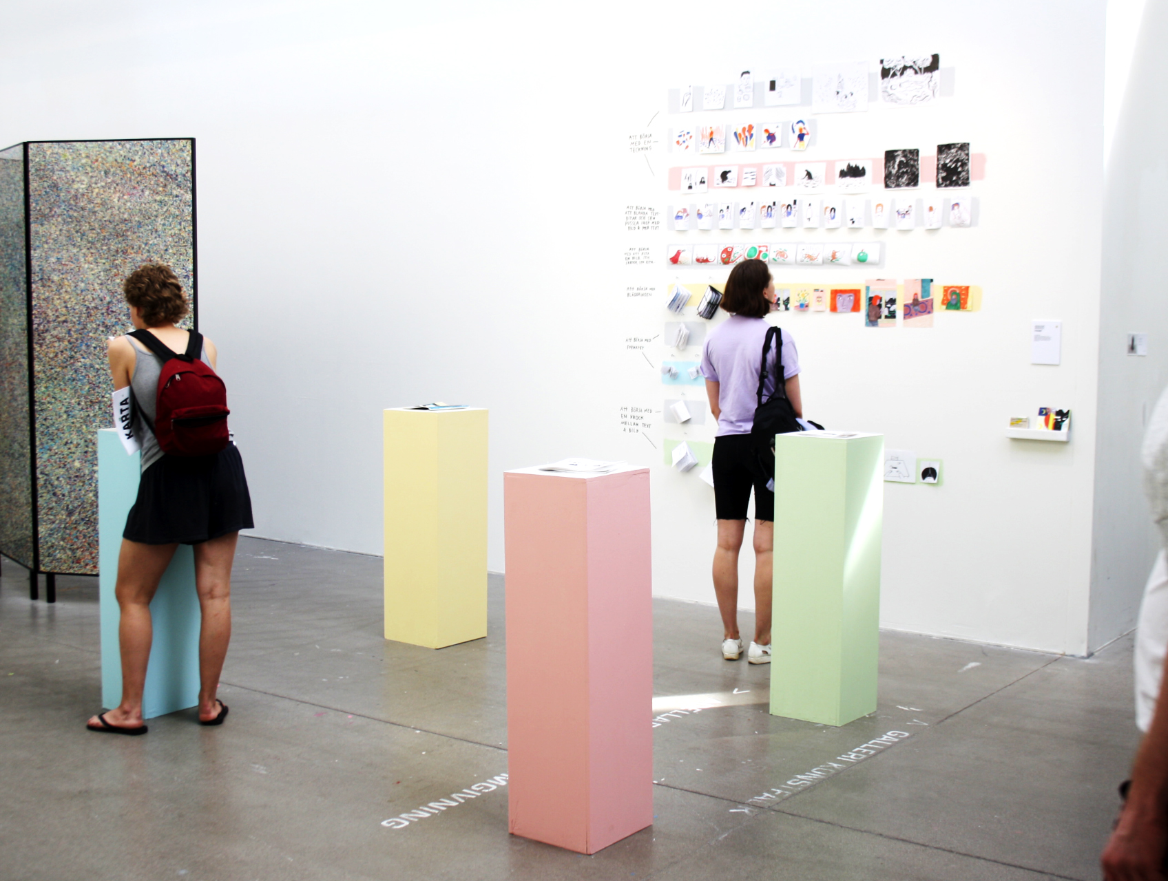 Each book presented on a podium, with a color corresponding with a line on the wall.