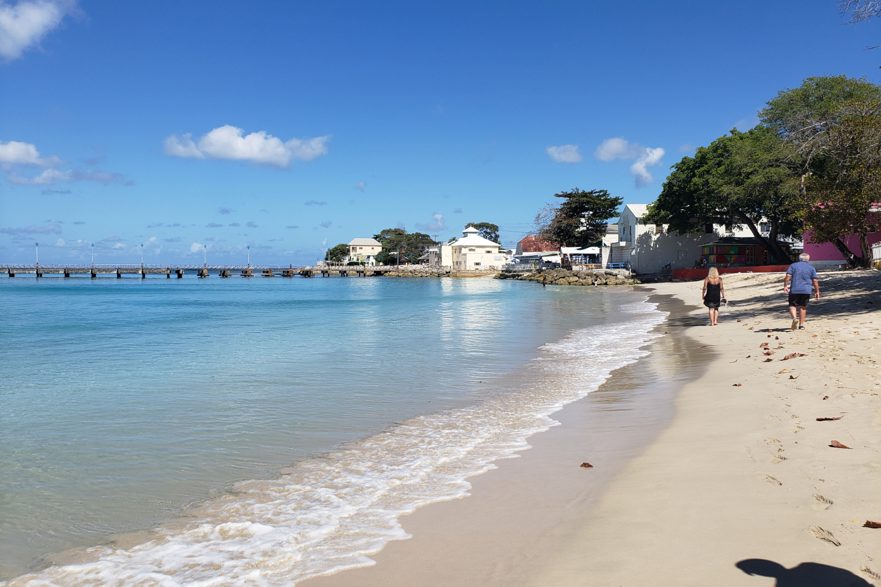 Jerry and Joy walking on the beach in Speightstown