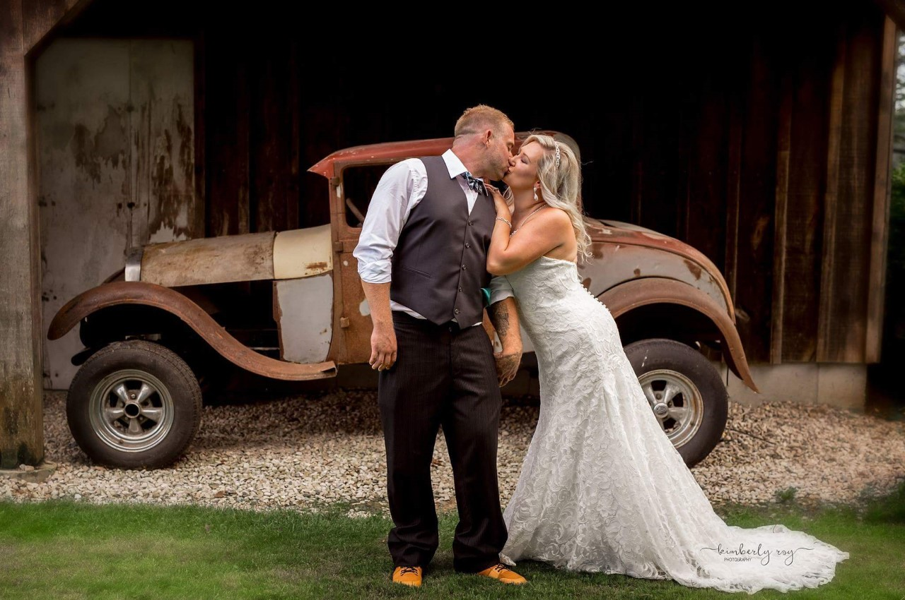 Carlene and Gord Ficht,  A Once Upon A Time Weddings bride with her groom, using an antique car as decor at their wedding.