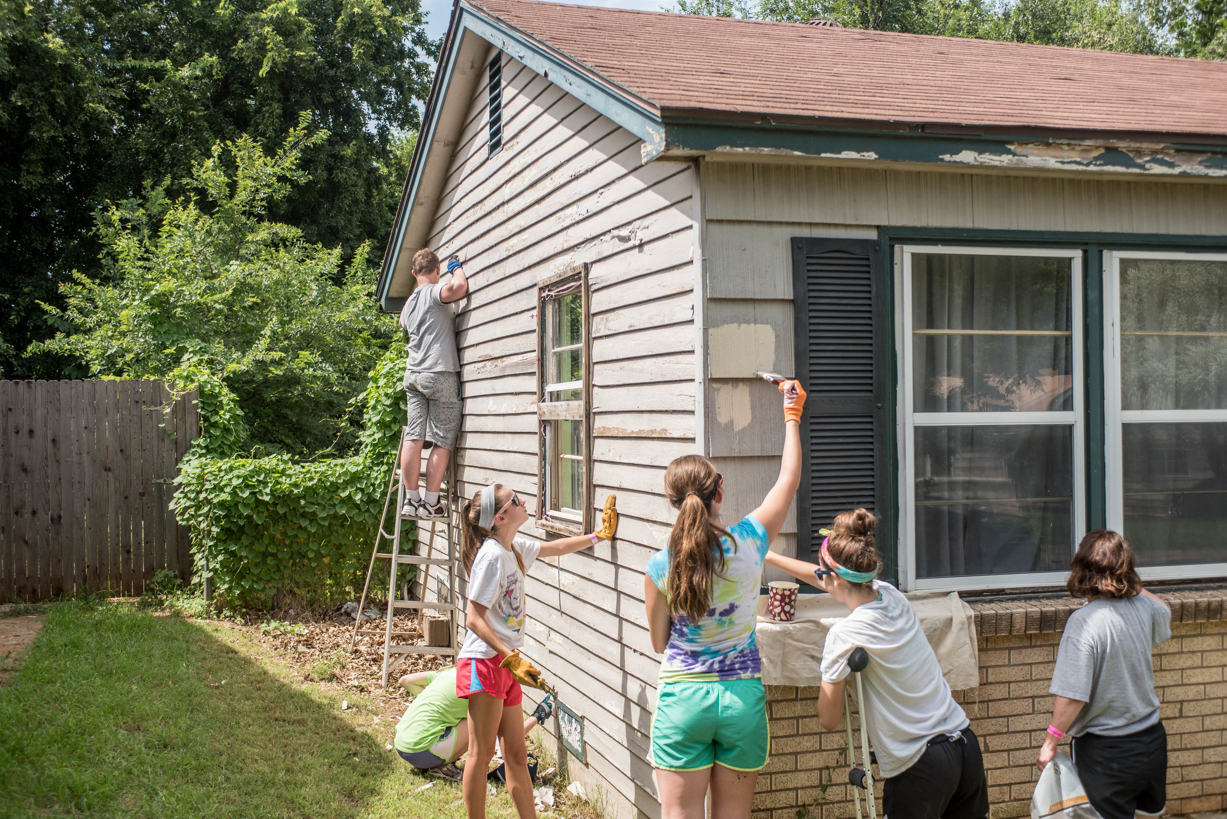 Volunteers paint a house for an elderly woman in Oklahoma City to prevent eviction and citation.