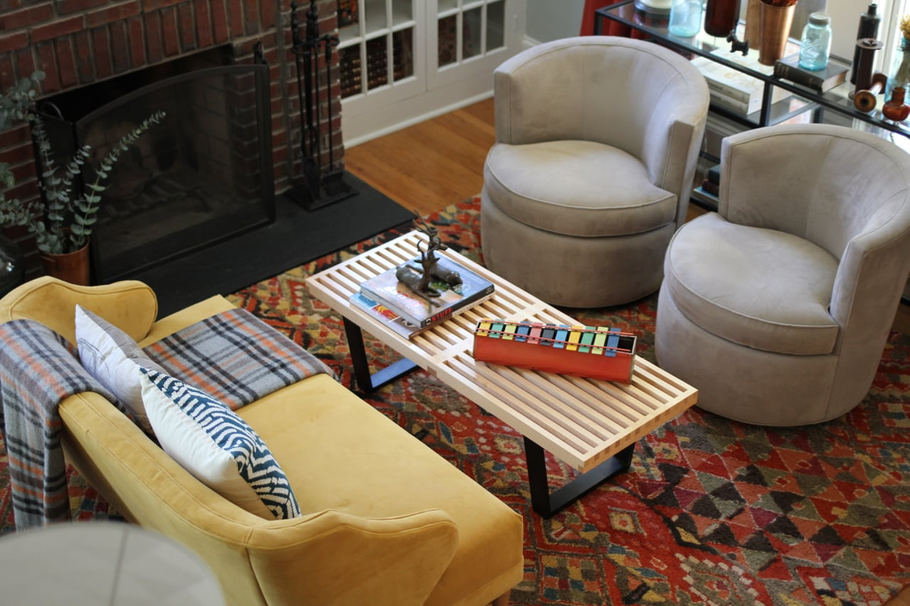 Pictured: West Elm Settee [currently not available, but they seem to bring it back occasionally!], Herman Miller coffee table:  thrift store find of the century! , Room & Board swivel chairs, Pottery Barn rug