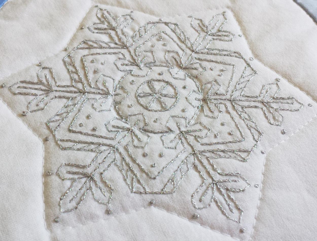 Large snowflake on the quilt using Kreinik floss.
