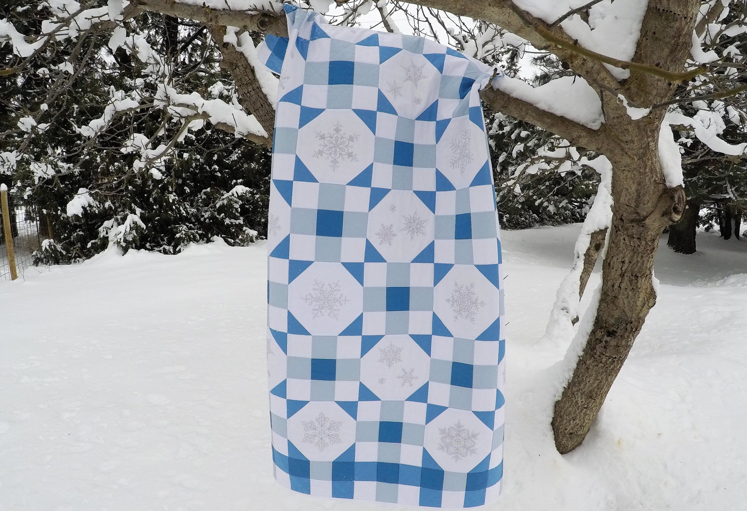 Falling Snow quilt pattern with embroidered snowflakes.