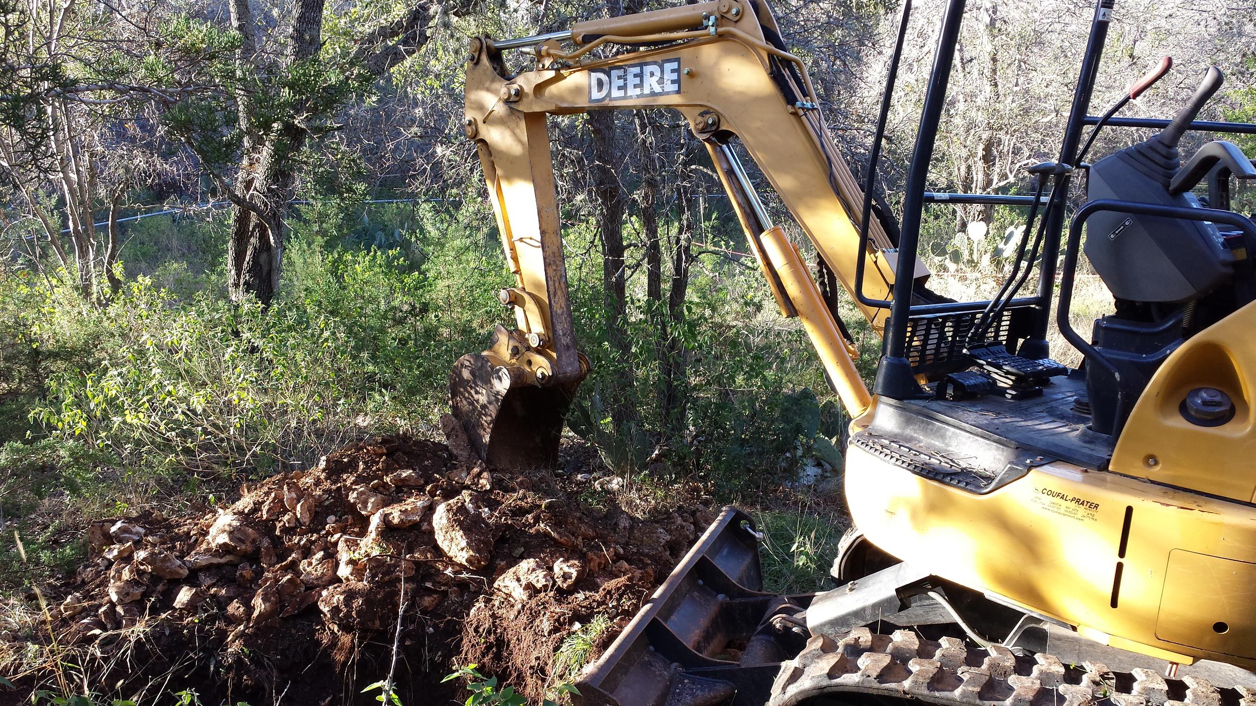 Excavator digging profilepits for foundation design.
