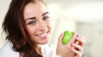 stock-footage-joyful-young-woman-eating-green-apple-is-healthy.jpg
