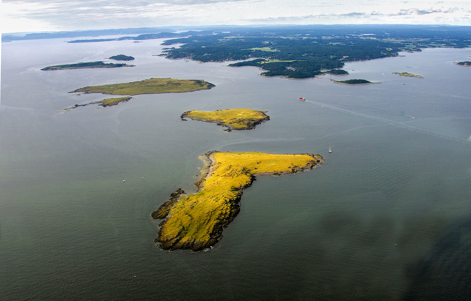 The three Sletter islands (Store Sletter, Midtre Sletter and Søndre Sletter) located southwest of Larkollneset, confirm their kinship with the other islands along the Østfold coast. A reddish, sharp and gnarled conglomerate of rhomb porphyry is sticking up in the day.The islands are a collection of flat, grassy islands off Larkollen. They can only be reached by boat, but docking is easy on all islands. Store Sletter has an especially nice sandy beach.