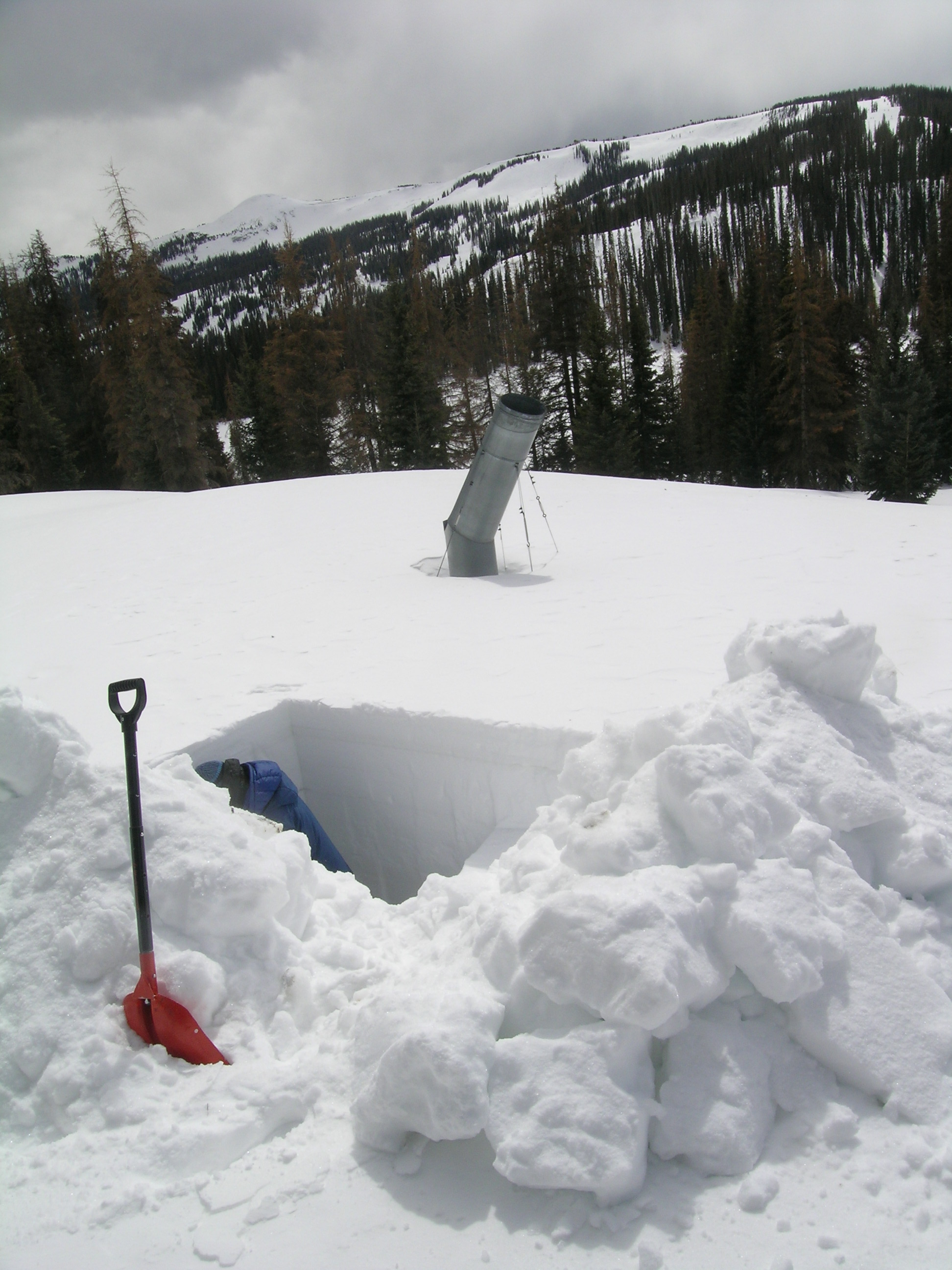 Andrew Temple digs deep at Wolf Creek Pass CODOS Site, March 23, 2013. The site adjoins an abandoned bulk snow sampling collector.  The Wolf Creek ski area is seen in the distance.