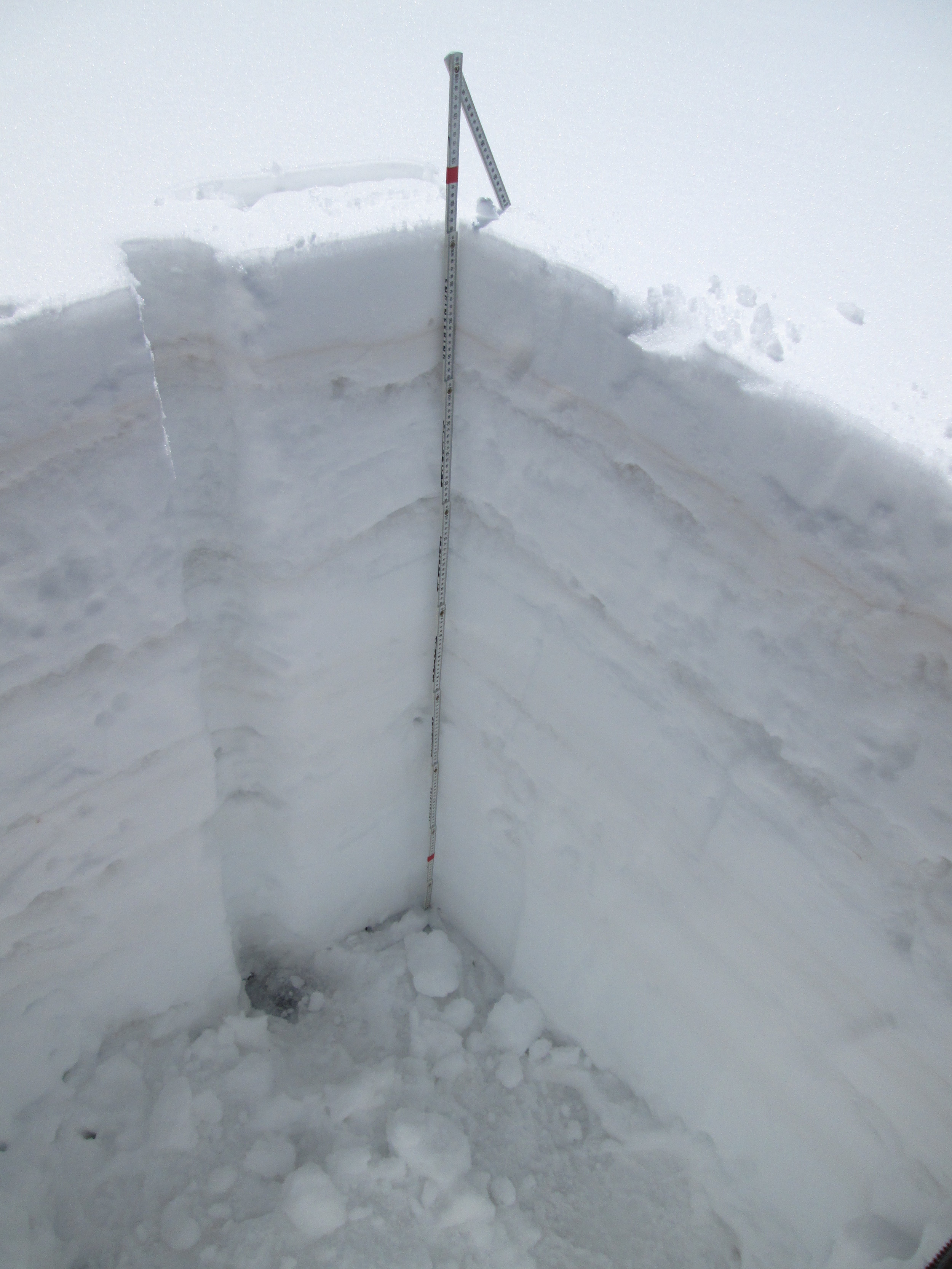 "The March 29 snow profile at the Wolf Creek Pass CODOS site.  Dust layer D3-WY2014 is clearly visible in a diffuse band 6"" below the snow surface.  Dust layer D2 may have been present in the thick layer of ice just below D3, but was not visible.  Dust layer D4 (March 30) fell onto the clean snow surface seen in this profile, significantly reducing snow albedo until fresh snowfall beginning today (April 2) began to bury D4.  Once re-exposed, radiative forcing in layer D4 will need to melt approximately 1"" of underlying SWE before merging with layer D3, reducing snow albedo even further."