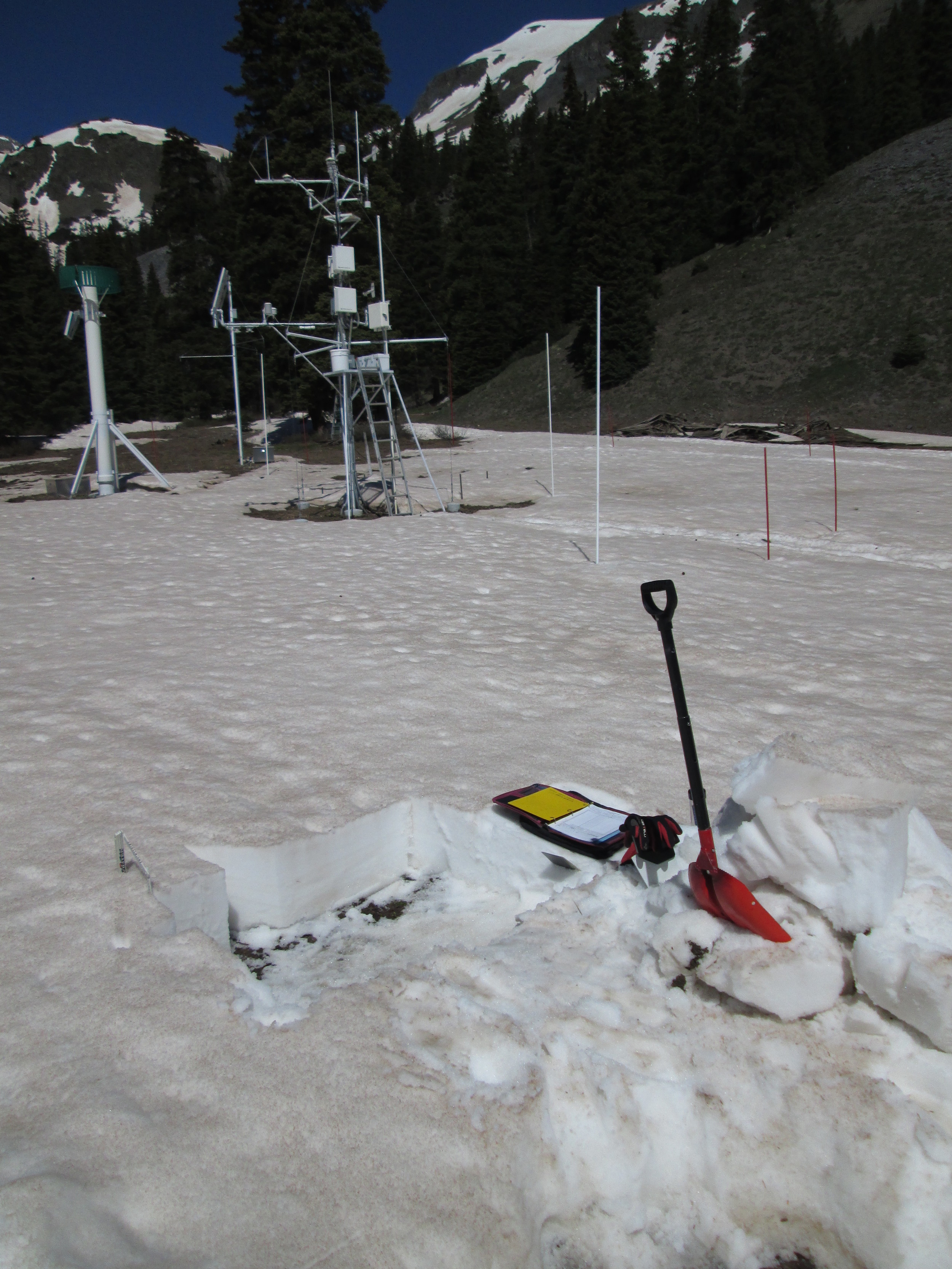 """Our final snow profile of the season at Swamp Angel Study Plot (SASP) on June 5 documented the loss of almost 30"""" (75 cm) of snow depth and 13.9"""" (352 mm) of SWE since the preceding snow profile on May 28. Even with a few lingering inches of clean snowfall from the Memorial Day weekend storm, and that brief restoration of high snow albedo, snowmelt had averaged 1.7"""" (44mm) of SWE per day during that 8-day interval. Snowmelt around the instrument mast was somewhat more rapid and had already revealed bare ground. The remaining snowcover and 5"""" of SWE seen in this snow pit was all gone within 48 hours."""
