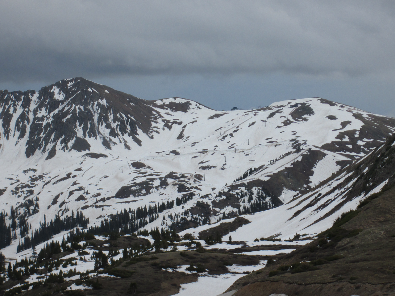 This view on June 16, 2015 of the upper Arapahoe Basin ski area, recently closed, clearly shows the concentration of Colorado Plateau dust in patches produced by wind drifting during wet dust-in-snow deposition on lee slopes, where blowing new snow containing dust decelerates and deposits.