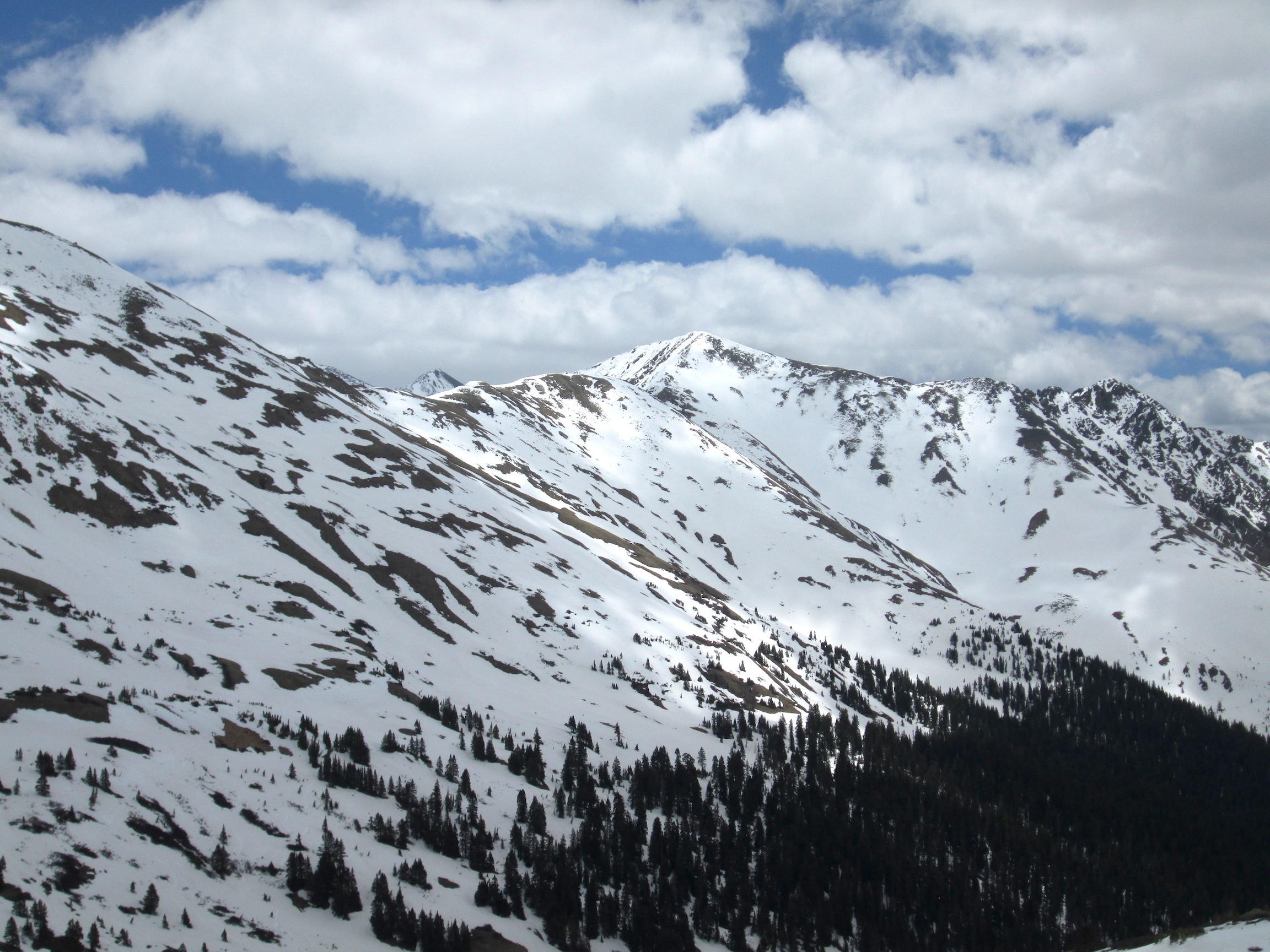 Loveland Pass on June 1. With thinning snowcover, solar radiation absorbed by the ground and vegetation are then re-emitted as thermal (longwave) energy, and rapidly accelerating snowmelt around their perimeter.