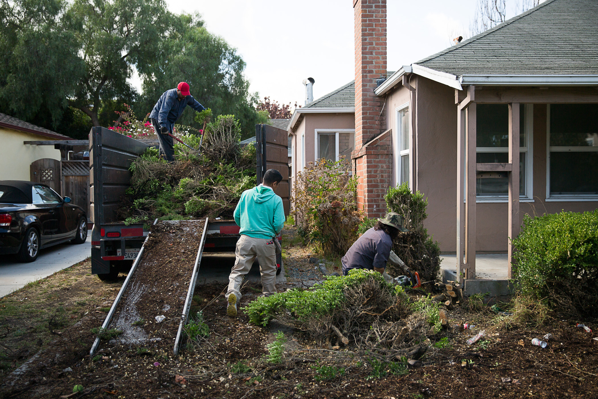 The landscaping crew rids the front yard of unsightly junipers to enhance its curb appeal.