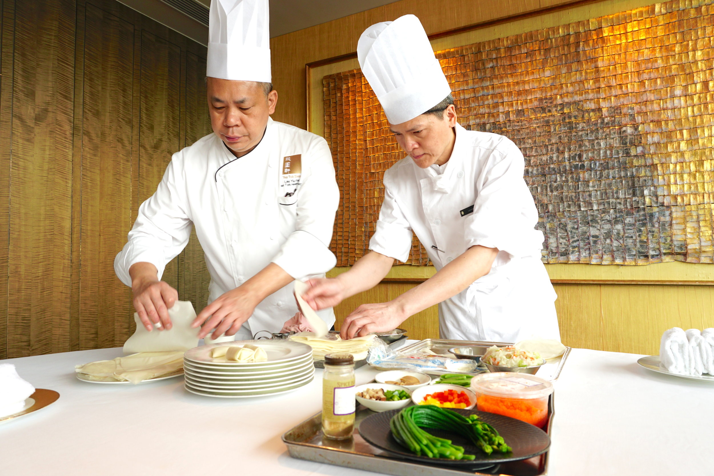 "Sharpening his knife and practicing the art of Cantonese cooking since the age of 14 in renowed Hong Kong dim sum kitchens, Executive Chef Lau Yiu Fai {left} is ""the"" guy you want folding, frying, and obsessing over your steamed pork and prawn dumplings."