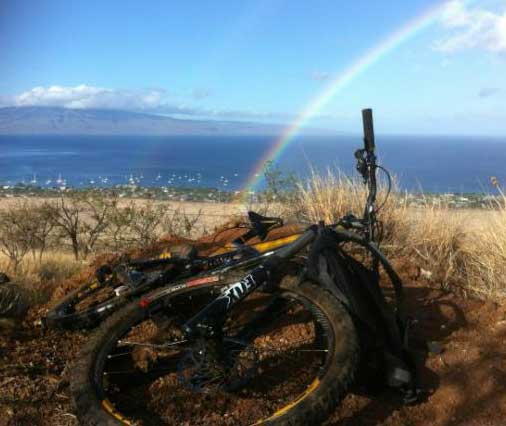 Maui bike ride with rainbow at top of trail. Performance Maui bike rentals.