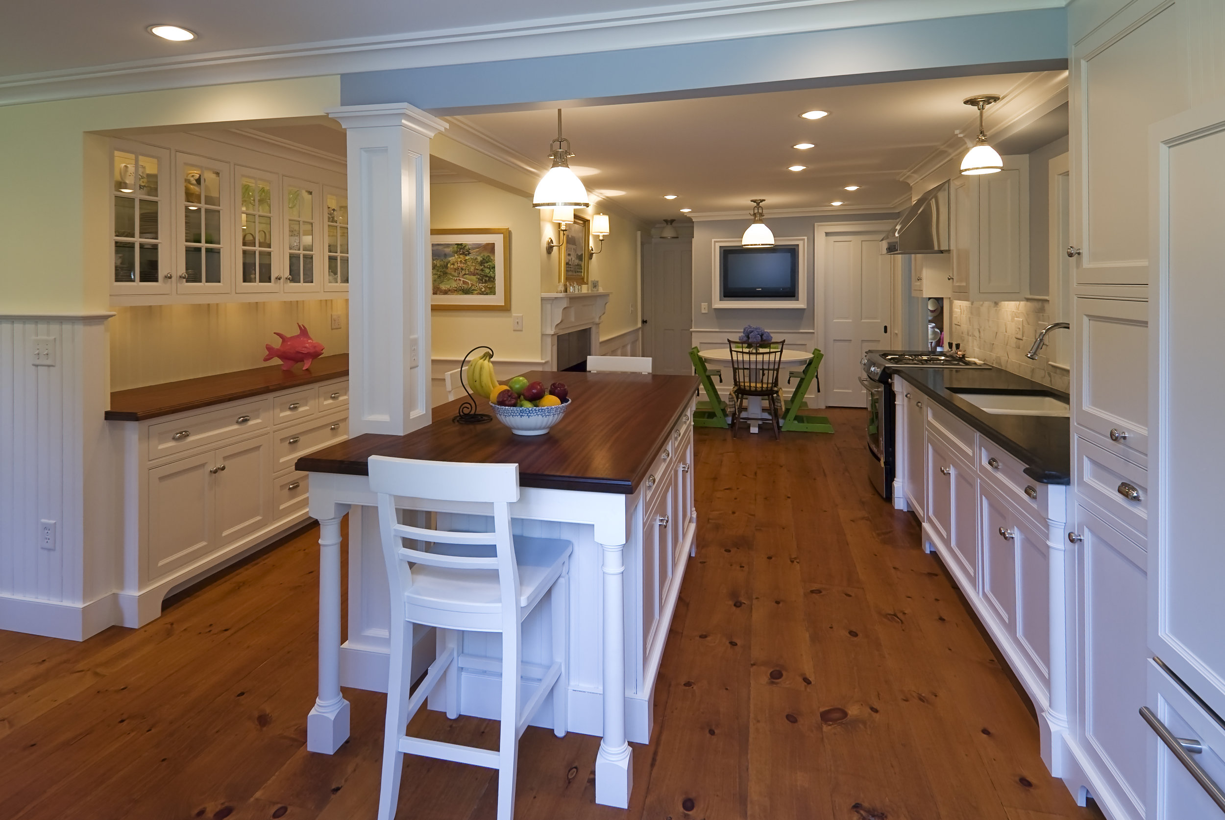 New mahogany counters are a great contrast to the bright white cabinets while complimenting the wide oak wood floors.