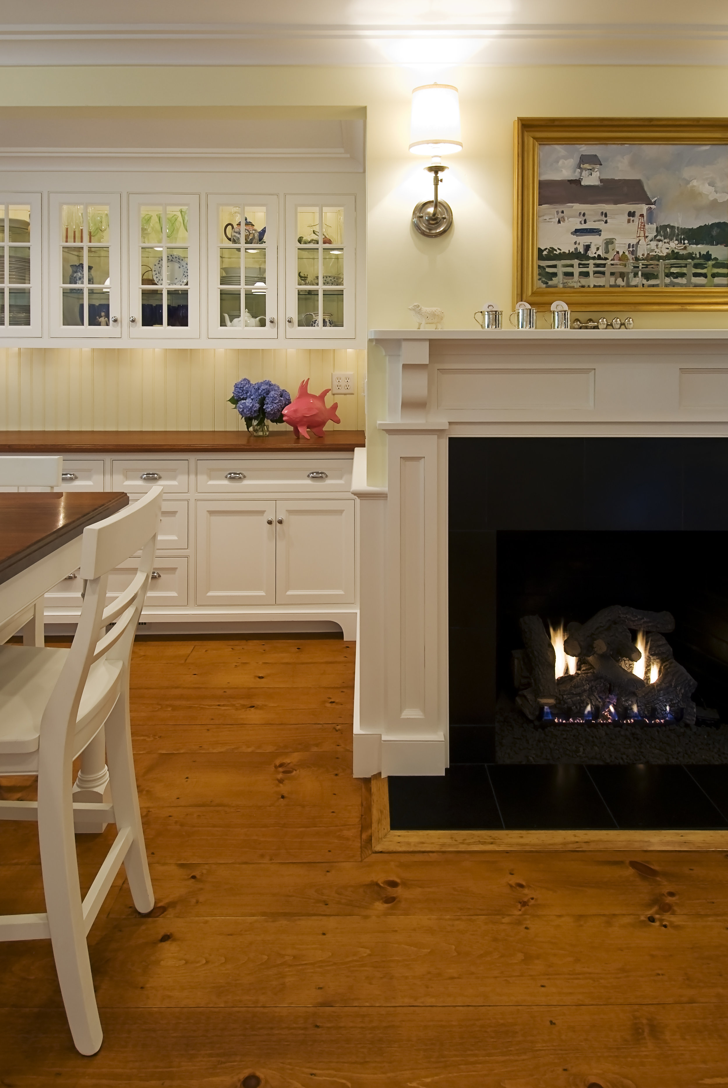 The custom built inset cabinets create an beautiful modern feel to this cozy kitchen. The old fireplace was renovated for a gas and new wide plank wood floors were added to keep the feel of the old farm house.