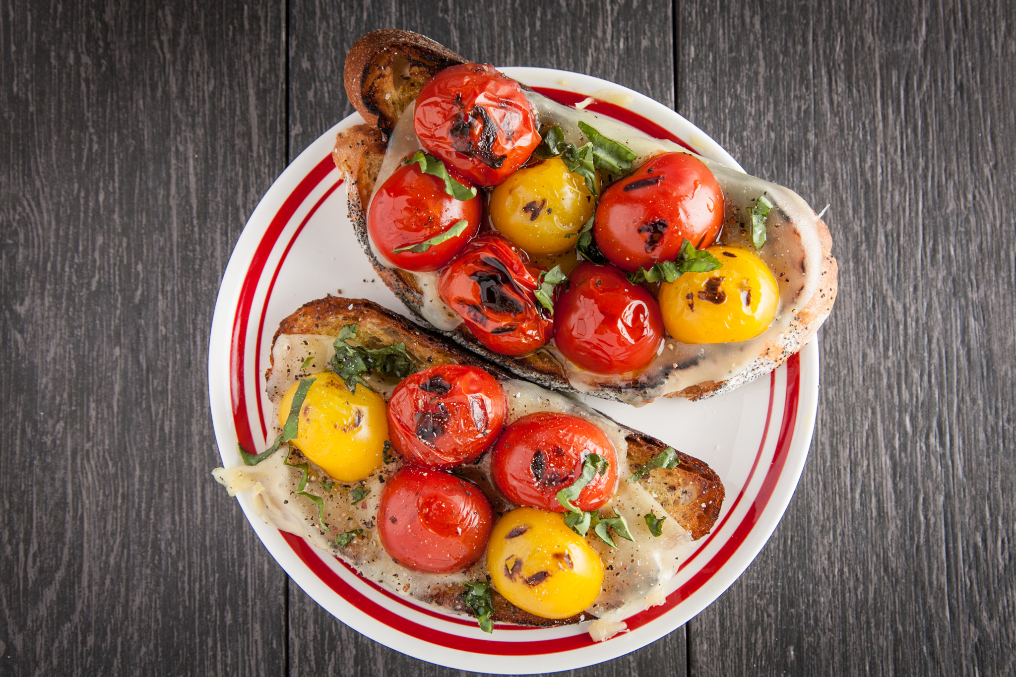 Roasted cherry tomatoes on grilled french bread, with a dab of spicy hot oil and a few shavings of basil