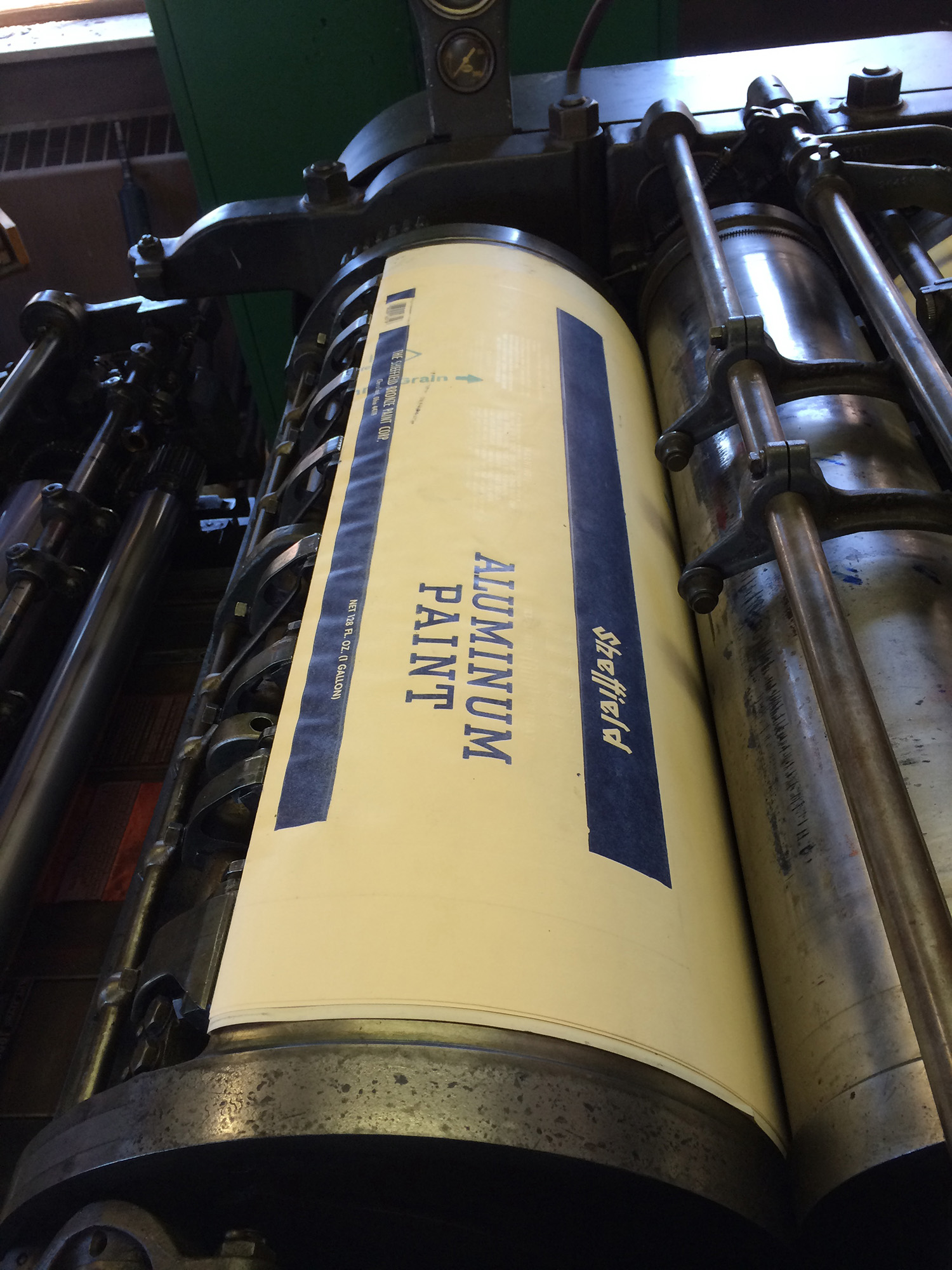 Printing of a paint-can label on a giant Miller tympan