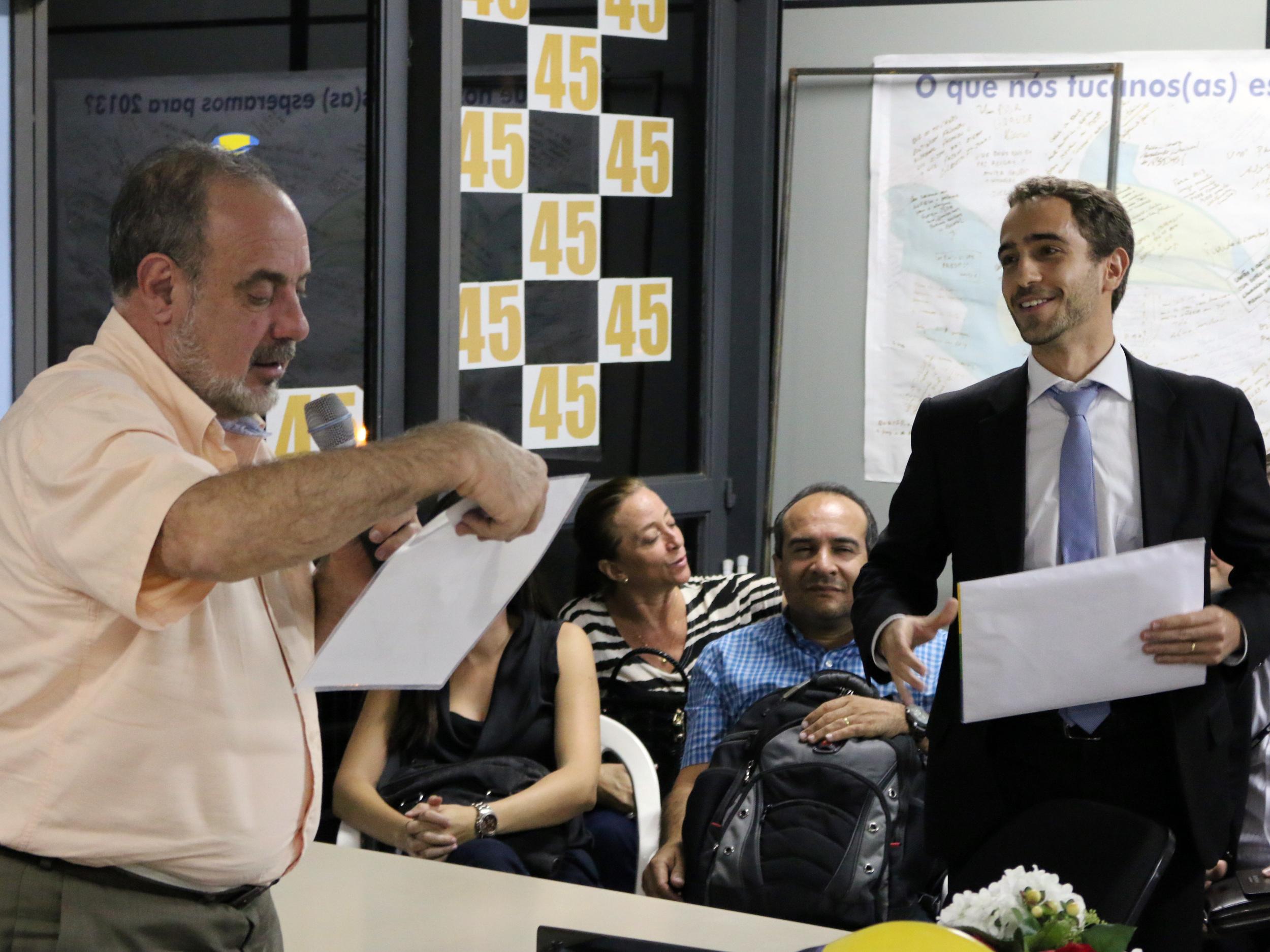 Matheus Azevedo entrega material de apresentação da Carreira de EPPGG a Fuad Noman. Foto: Filipe Calmon / ANESP