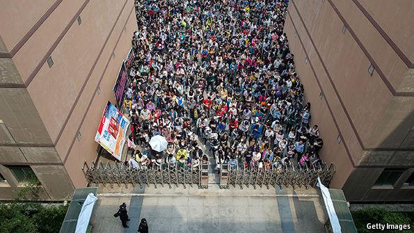 Candidatos a cargo no serviço público chinês se aglomeram na entrada do local do exame. Foto: Getty Images