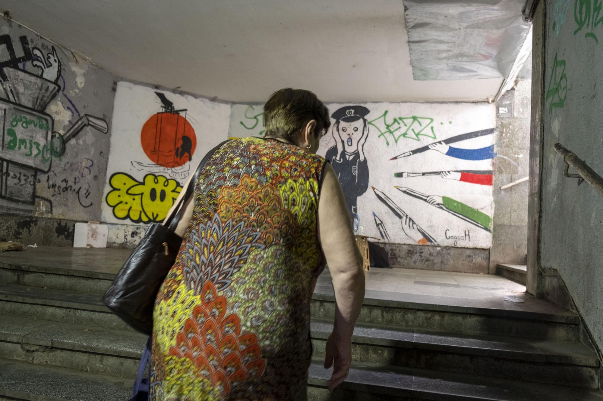 woman walking up stairs with graffiti.jpg