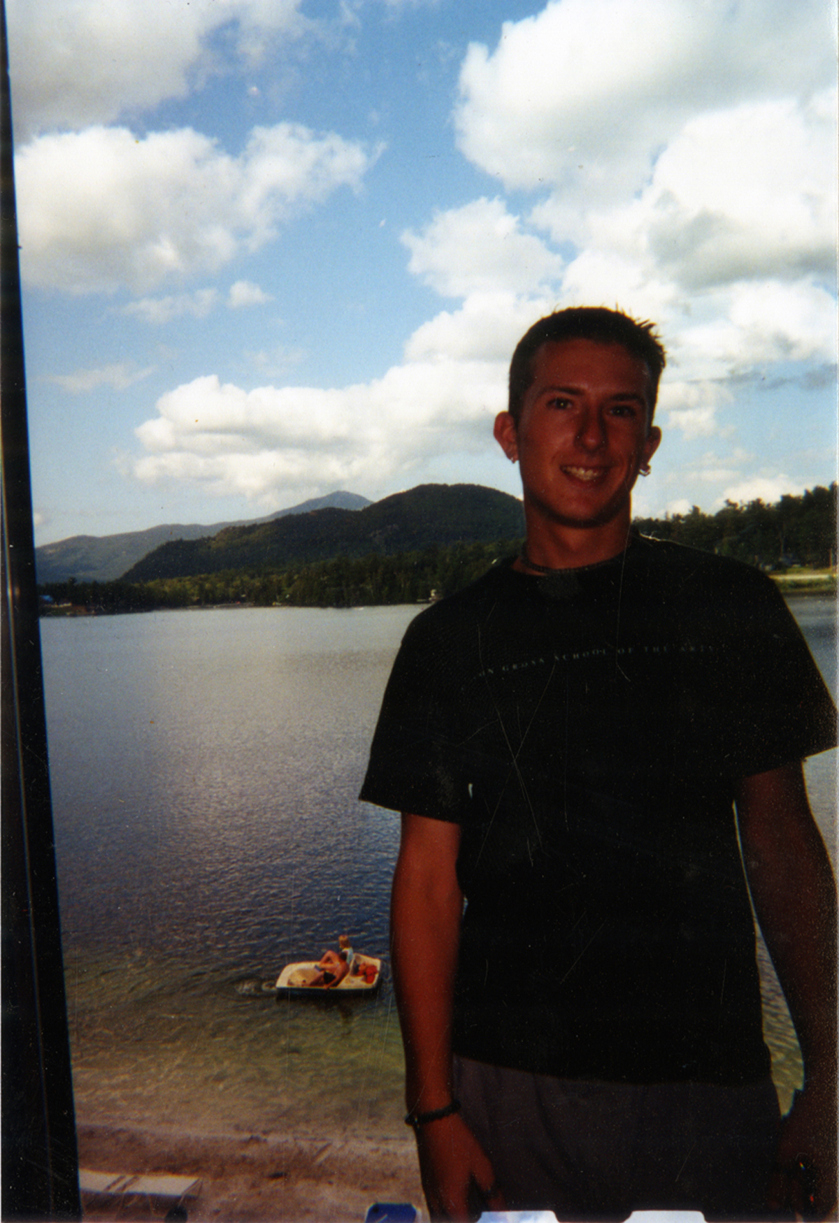 """Artifact #1 - Portrait of the artist on family vacation in 2000, wearing """"Mason Gross School of the Arts"""" t-shirt; 3"""" x 5"""" color snapshot."""