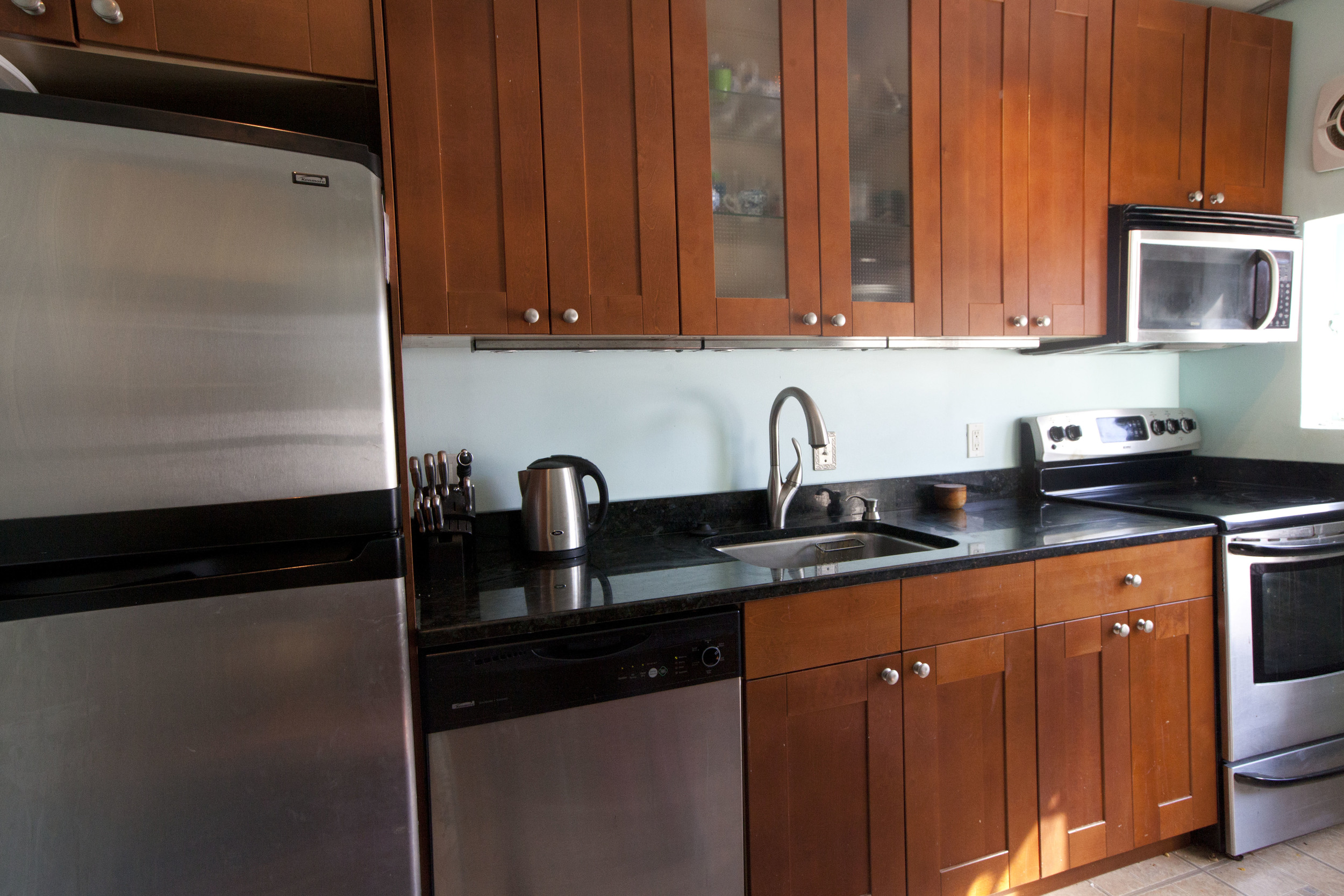 Kitchen has dark granite and full-sized stainless steel appliances.