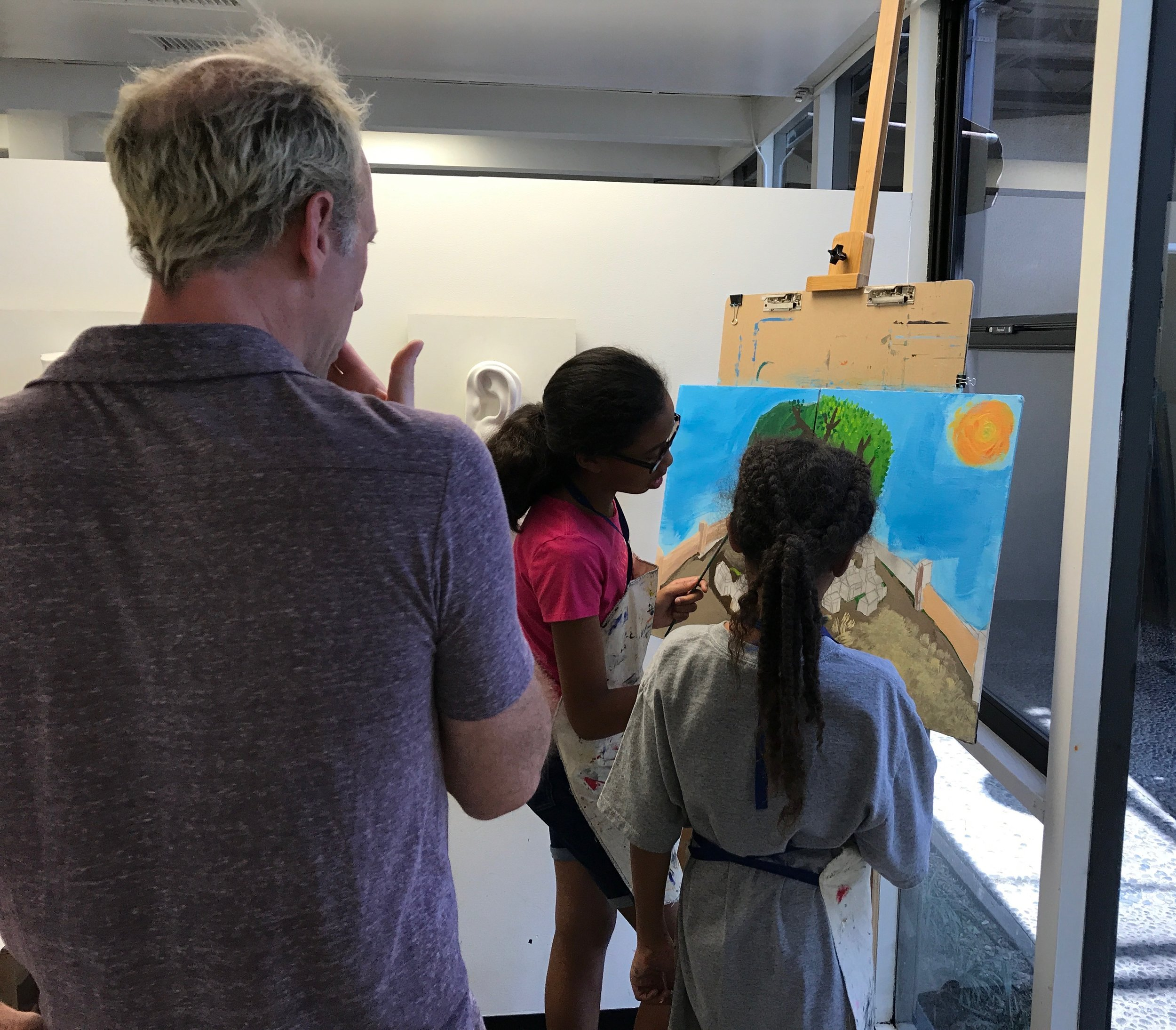 Two sisters create a painting together while teacher Steve provides tips and instruction.