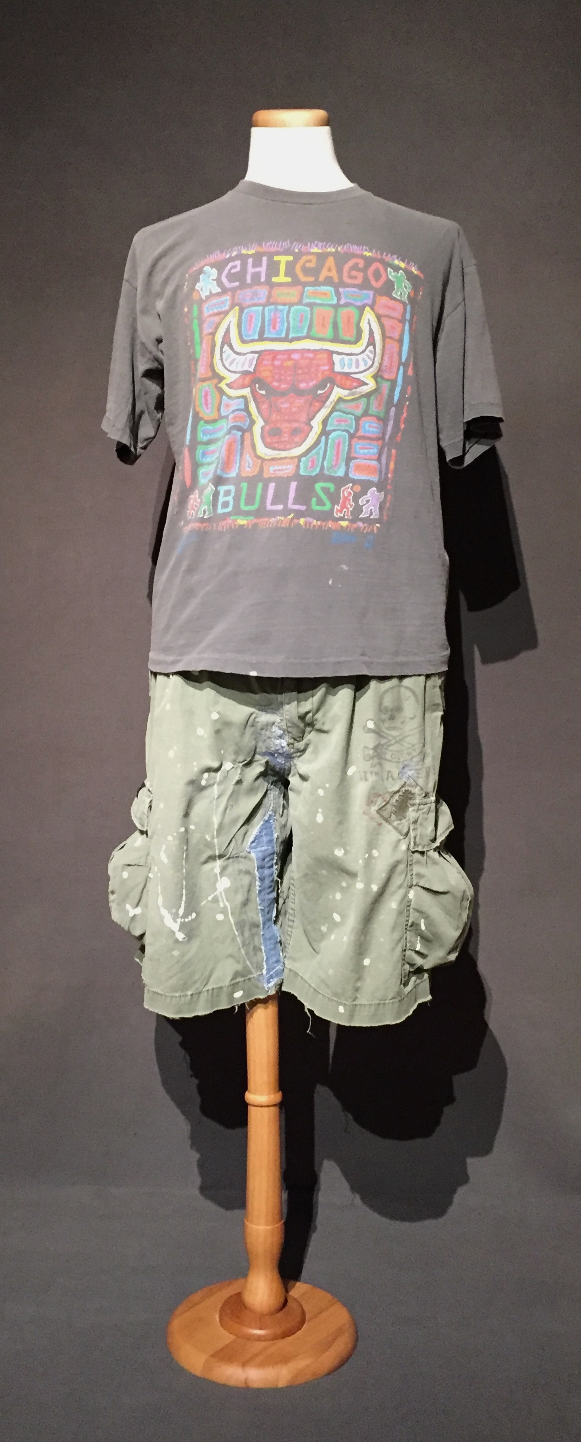 """- Chicago Bulls t-shirt, hand-repaired cargo shorts; Owner – Cyndi, lesbian, woman, 42, lives in Iowa; c. 2010sThis is a typical casual outfit worn by Cyndi and she related her feelings about how her sexual identity influences her style, """"I think in the past it did, because when I graduated from college I had really long hair, I was like, kind of a hippie, and then eventually, when I came out, it just every year, kept getting shorter and shorter and shorter and then for a while I did go short and spikey and my family was like, 'who's that guy?' I'm more comfortable with my hair short now. If I get my hair cut too short and [gasps] 'oh no, I look like a lesbian now and then I'm like wait, uh, maybe I look like a lesbian all the time?' So, my clothing, is typically pretty casual and then if I have dress clothes, it's pants, I never wear skirts. I don't own a skirt anymore. I don't own a dress, no pantyhose."""" – personal interview with Cyndi, November 21, 2017"""