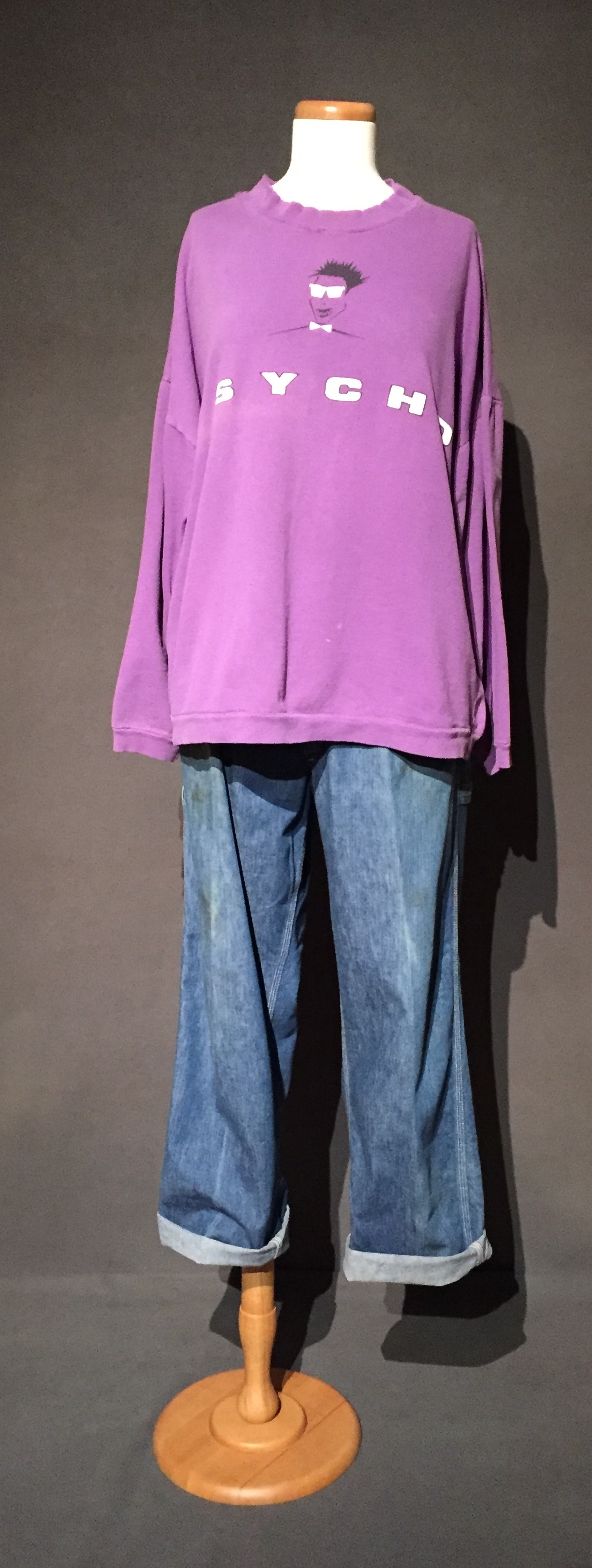 """- Purple """"psycho"""" sweatshirt, denim pants; Owner – Maren, bi-sexual, woman, 41, lives in Iowa; c. 1990sMaren explained that she """"physically presented pretty butch."""" This sweatshirt is a garment she wore in high school in the 1990s that she felt was indicative of her sexuality. She related experiences about other garments pictured in the case as well, such as flannels and Doc Martens when she said, """"I was walking with my girlfriend at the time, and I had a bottle thrown at me in Iowa City. I was wearing cut-offs, Doc Martens, a tank top and a flannel over that. I was very clearly identified in their eyes as a lesbian."""" – personal interview with Maren, October 1, 2017"""