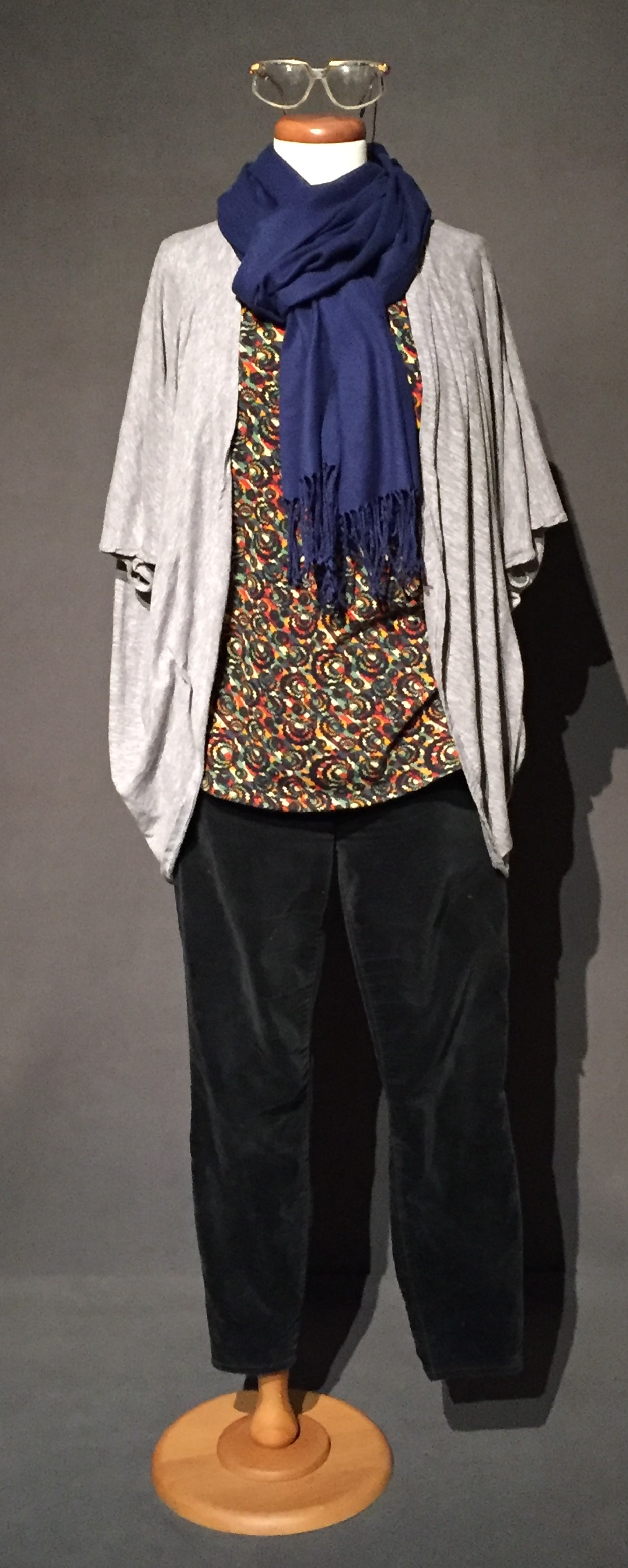 """- Black pant, flower print top, sweater, blue scarf, glasses, pink flatsOwner – Emma, queer lesbian, woman, 30, lives in Iowa c. 2010s""""I have always read as straight. People, even other queer people, read me as straight and so I have found that it doesn't particularly matter how I perform my gender or my identity. I am read as a straight woman, so I had to say out loud """"I'm gay,"""" or """"I'm a lesbian"""" or I'll talk about my girlfriend, and I'll have to be like very explicit. """"No, we have a joint checking account, it's a partnership, we're together, at night get in the same bed."""" I've had to be really vocal. I've gone through phases in my life, where I've tried to display my sexual orientation in a physical way, you know everyone always talks about, the baby dyke's first hair cut type of thing. I didn't have any sort of attraction to, I didn't want to butch up in anyway. Any attempt I've made to butch-it-up, is just like confusing for me and the people around me. I gave up with that, and so at this point, I have a lot to say, kind of about like, femme identity. I just have to say out loud a lot that I'm gay."""" – personal interview with Emma, November 4, 2017"""