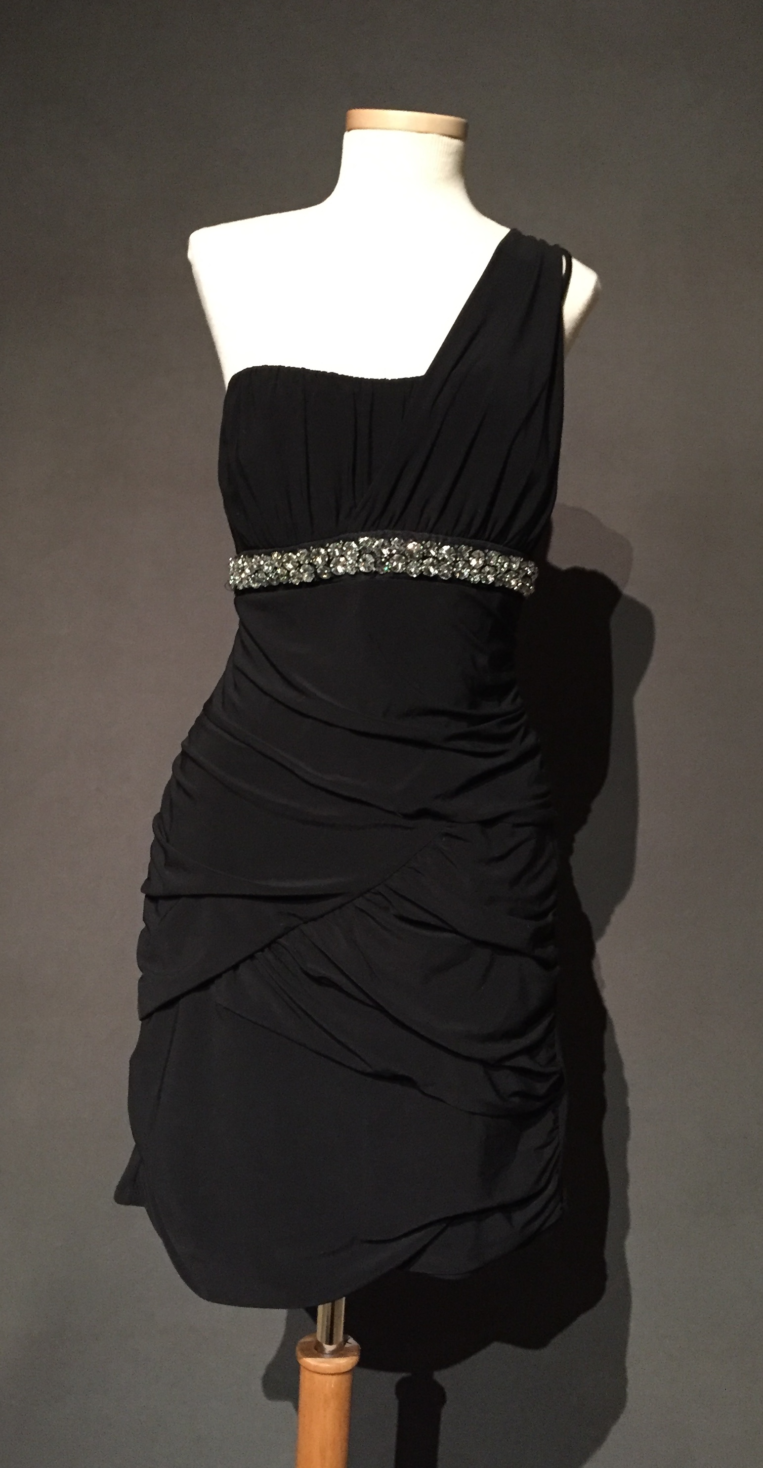 """- Black dress with rhinestone waistline Owner – Lyadonna, bi-sexual, woman, 32, lives in Iowac. 2010sLyadonna frequently wore this little black dress to her local gay bar and related, """"Oh yeah, yeah, River Wild was a drag king that I got friendly with because of this dress. It's my lucky dress."""" – personal interview with Lyadonna, October 5, 2017"""