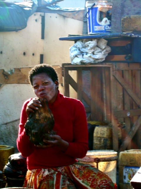 Local woman preparing goat for dinner and posing for the camera.
