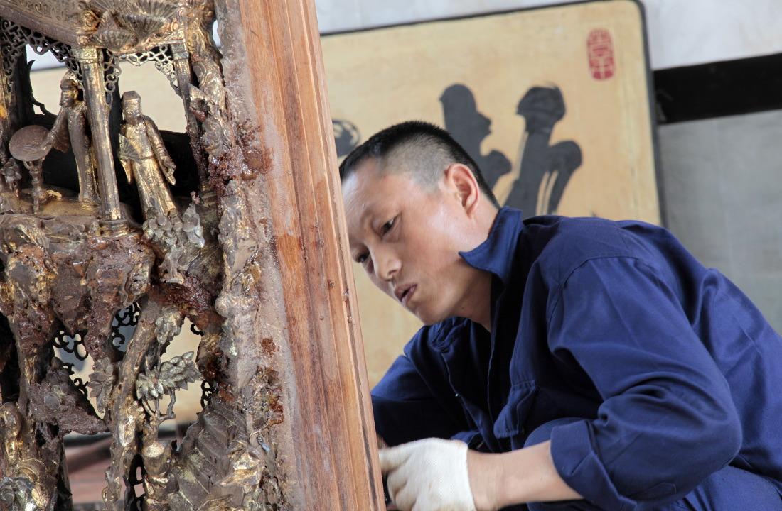 Pagode Nghia An Hoi Quan : un artisan travaille à sa restauration