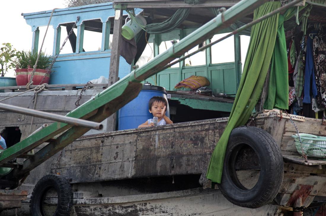 Un enfant attend, sur les marchés flottants de CanTho