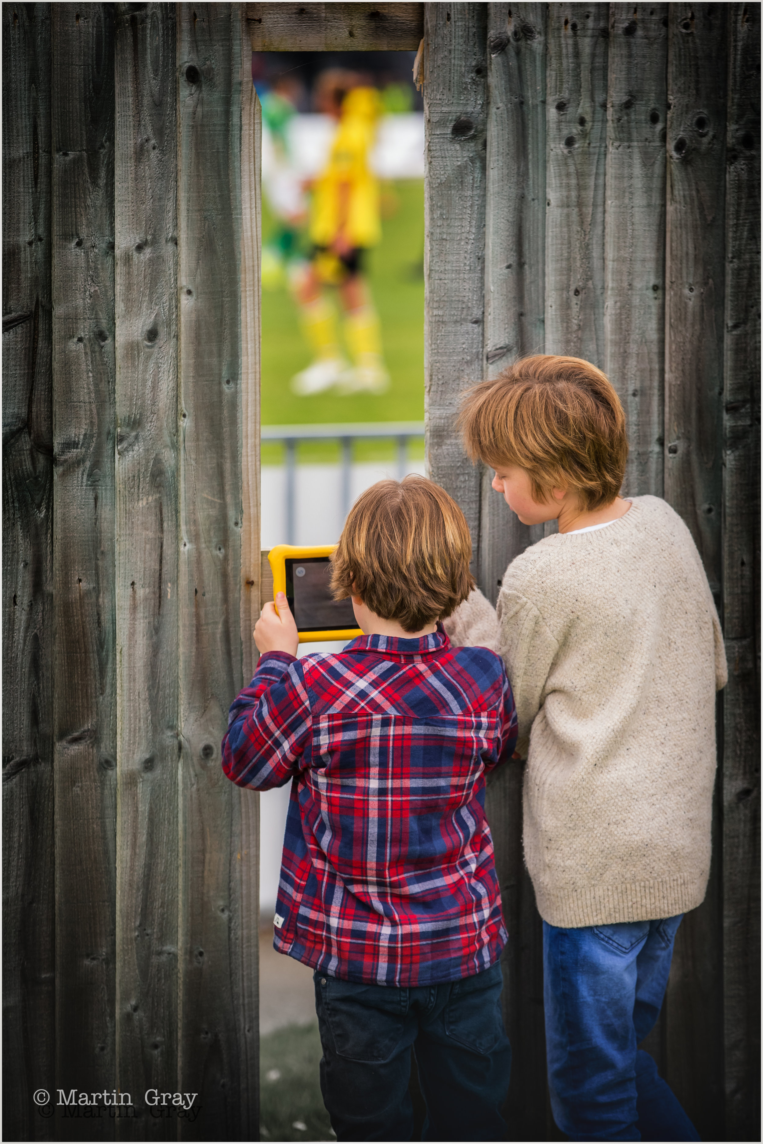 'Cheap Seats'… Two lads find a gap in the fence to watch and photograph a Guernsey FC game…
