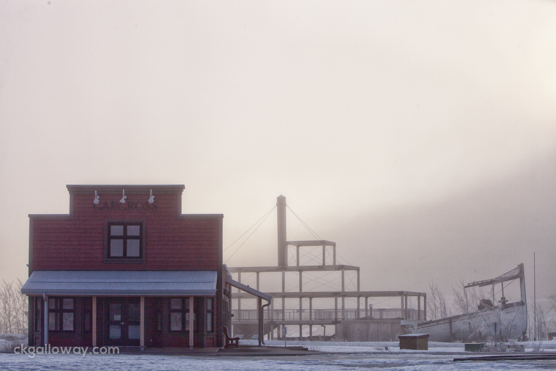 Carcross Visitor Information with a closed sign in the window and a spooky boat in the background.