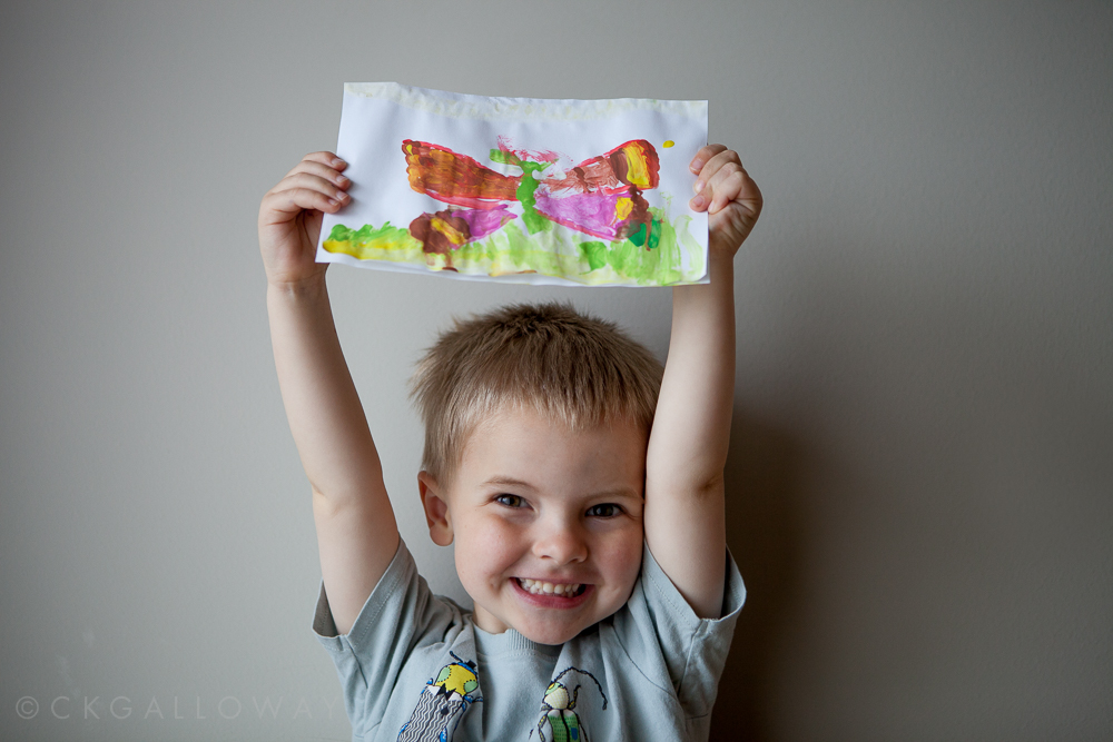 Oscar proudly displays his butterfly painting. Photo by Christa Galloway.