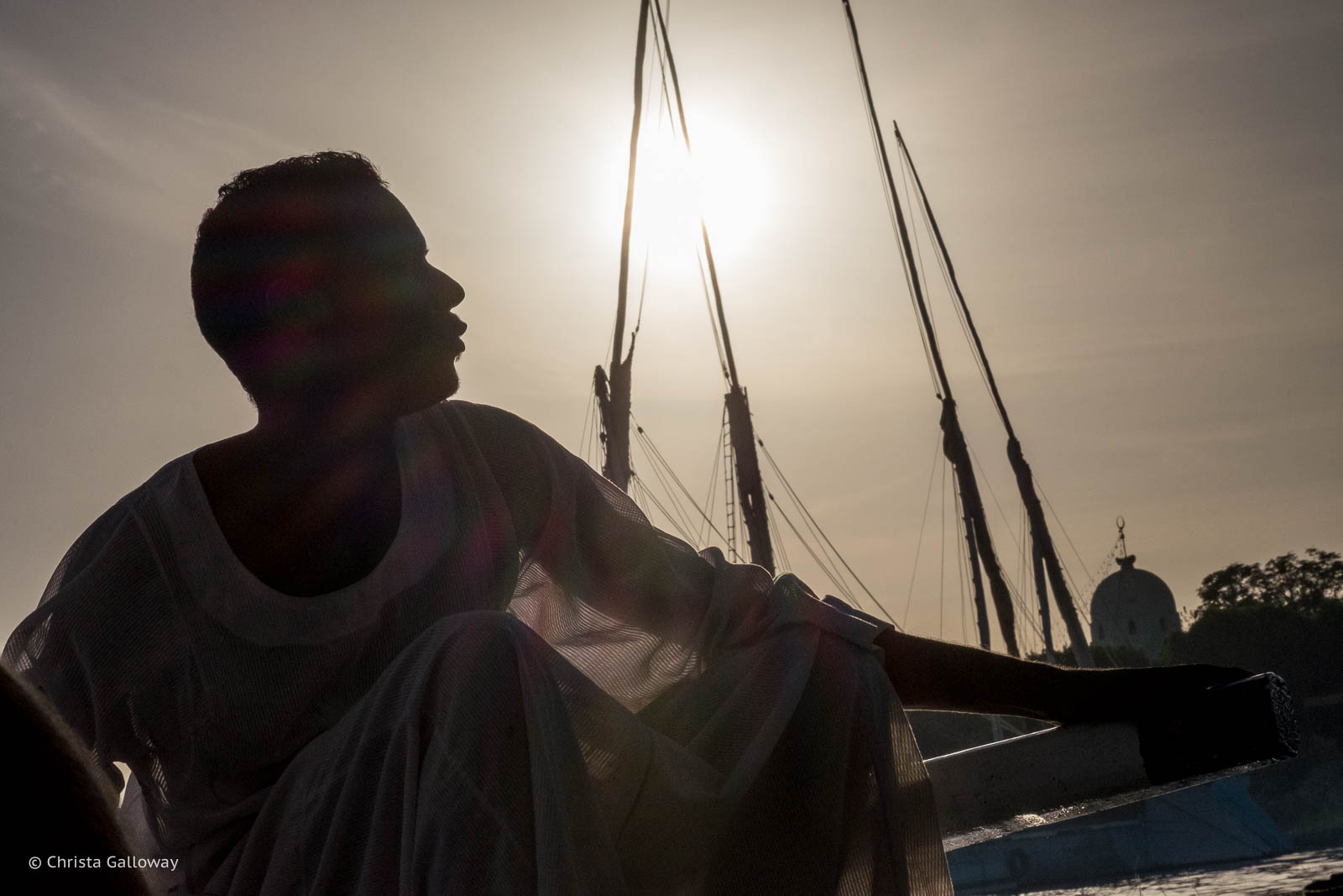 An Egyptian steers a felucca sailboat towards the west bank of the Nile.