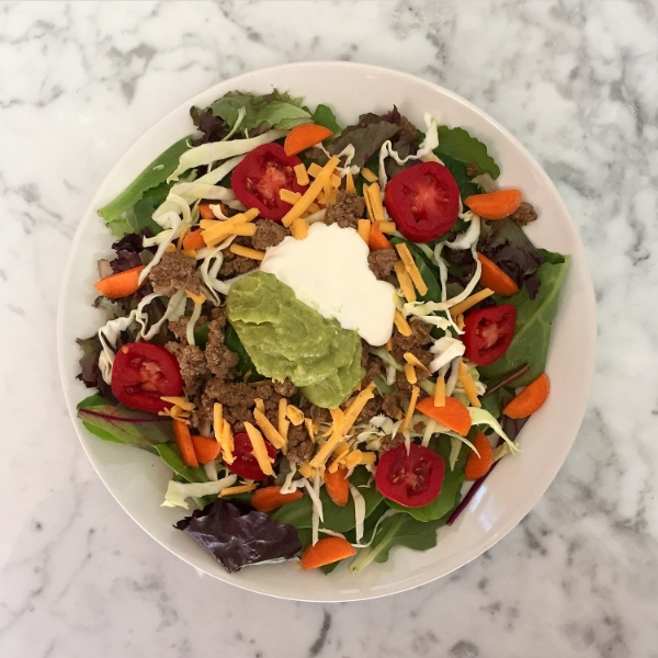 Fiesta Salad - seasoned ground grass-fed beef, tomatoes, carrots, cabbage, aged cheddar, organic sour cream, and guacamole!