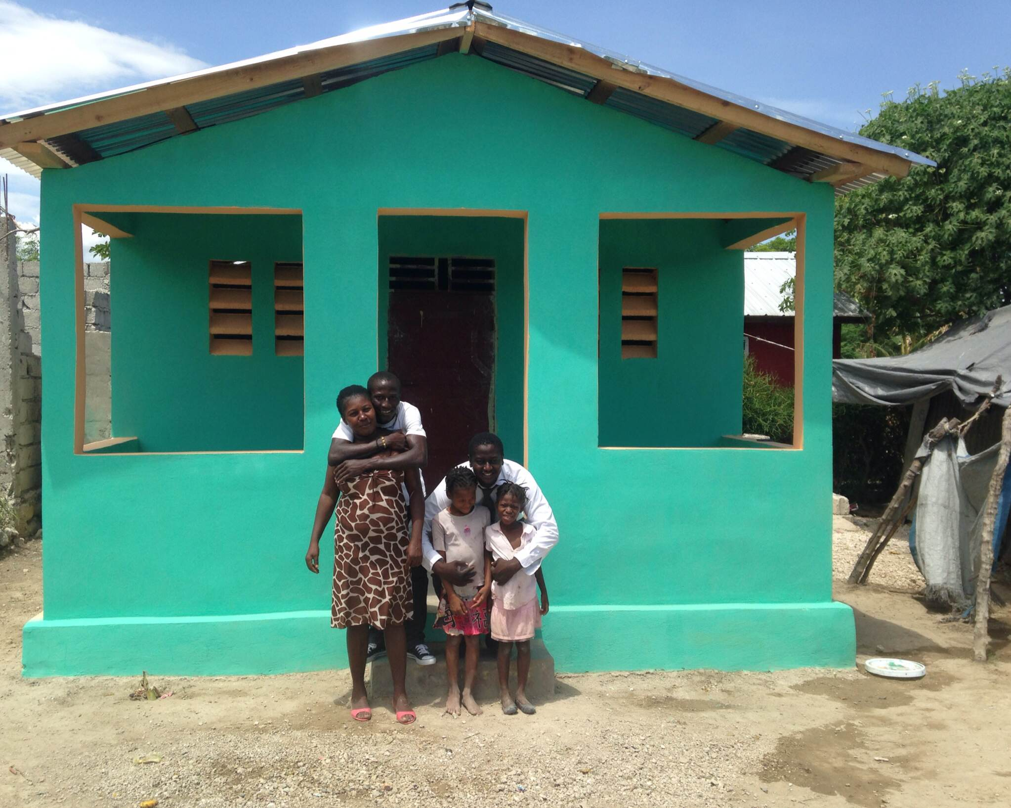 Maculla and her family with our In-Country Director, Jimmy, standing in front of their new home.