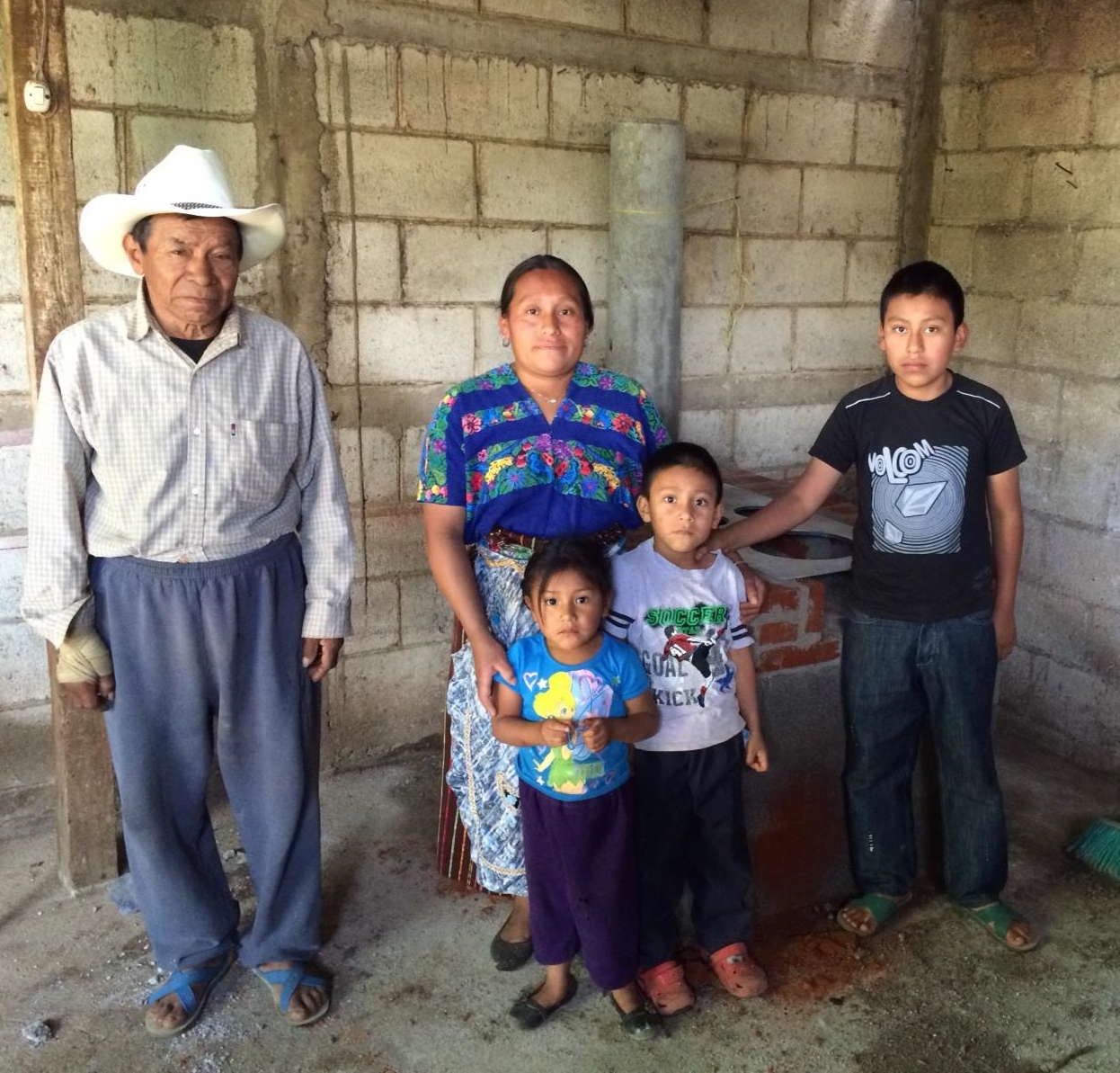 A Guatemalan family stands inside their new home in front of their new stove, both built by a team of Homes from the Heart volunteers.