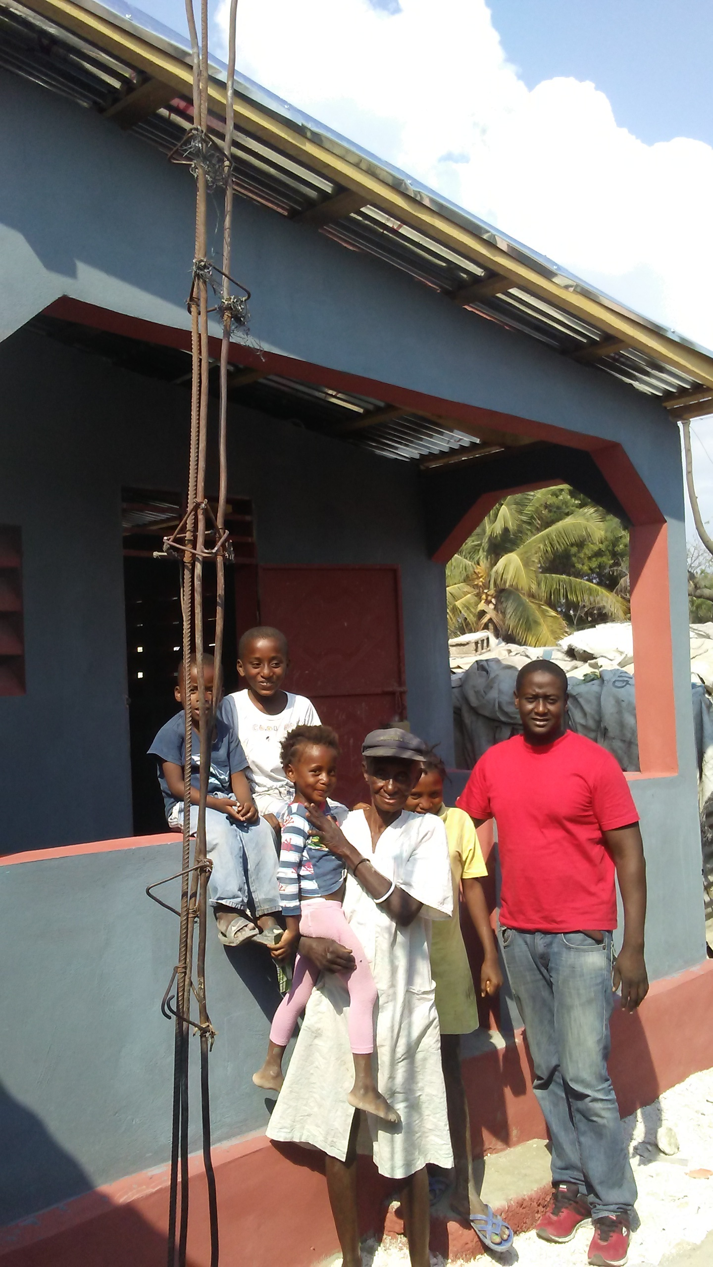 Lucienne Joseph with her grandchildren and Jimmy, Homes from the Heart's liaison in Haiti.