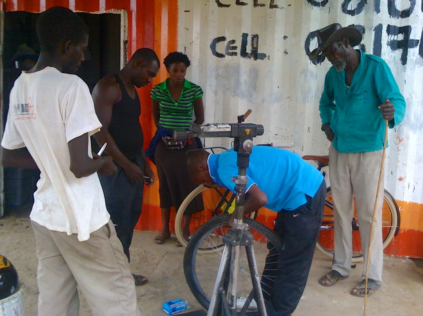 Sparks demonstrating how to do a tubeless conversion, a very valuable thing in these parts. Even Erasmus's father came out to see.