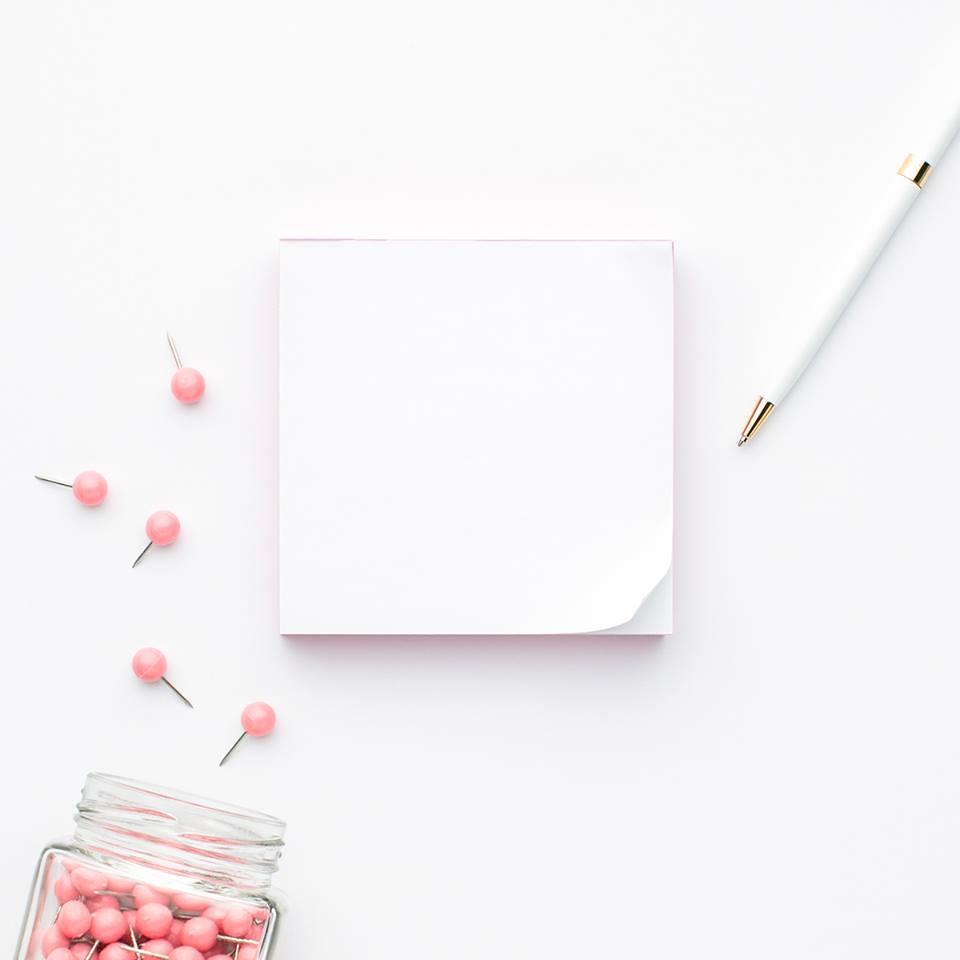 Photo of a note pad, pen, and thumbtacks