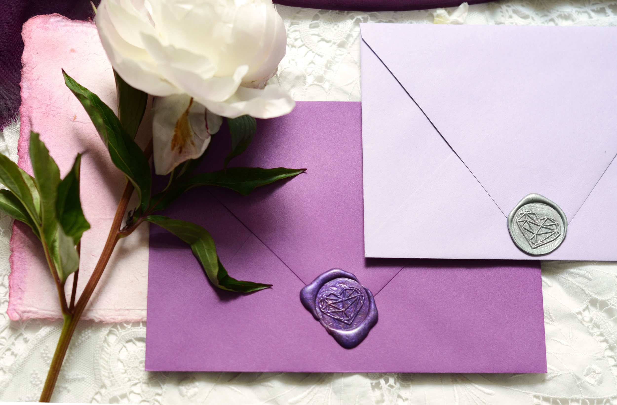 purple envelope flat lay with peony